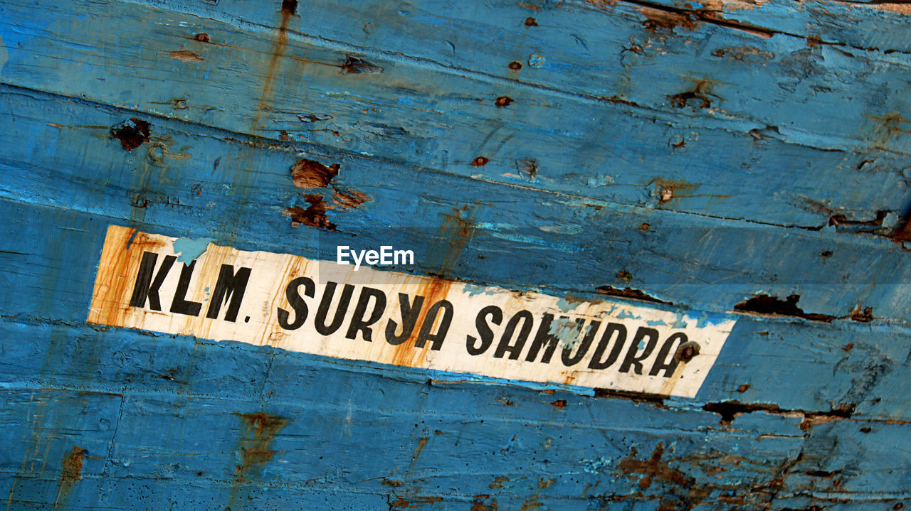 text, blue, weathered, old, no people, western script, rusty, communication, wood - material, full frame, close-up, metal, day, backgrounds, architecture, damaged, bad condition, outdoors, abandoned, run-down, ruined