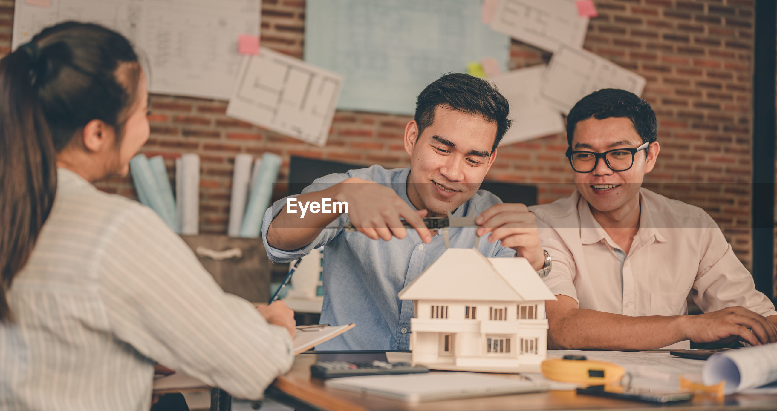 Colleagues discussing model home in office
