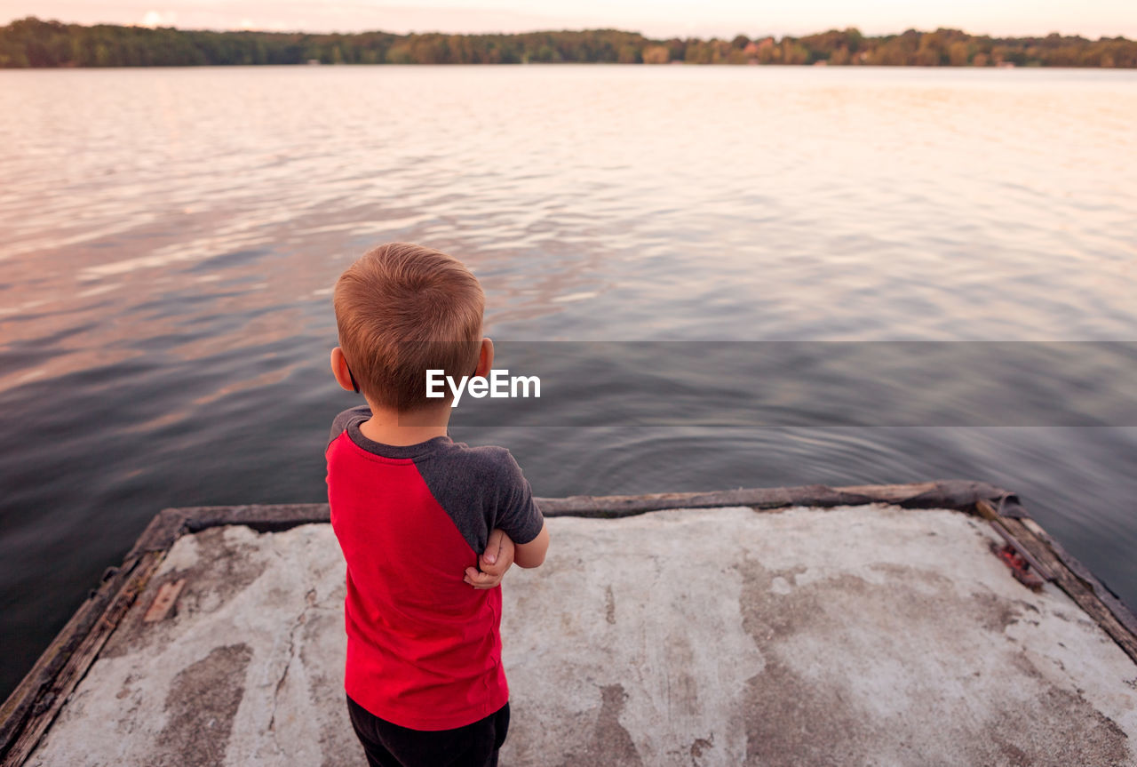 Rear view of boy looking at lake during sunset