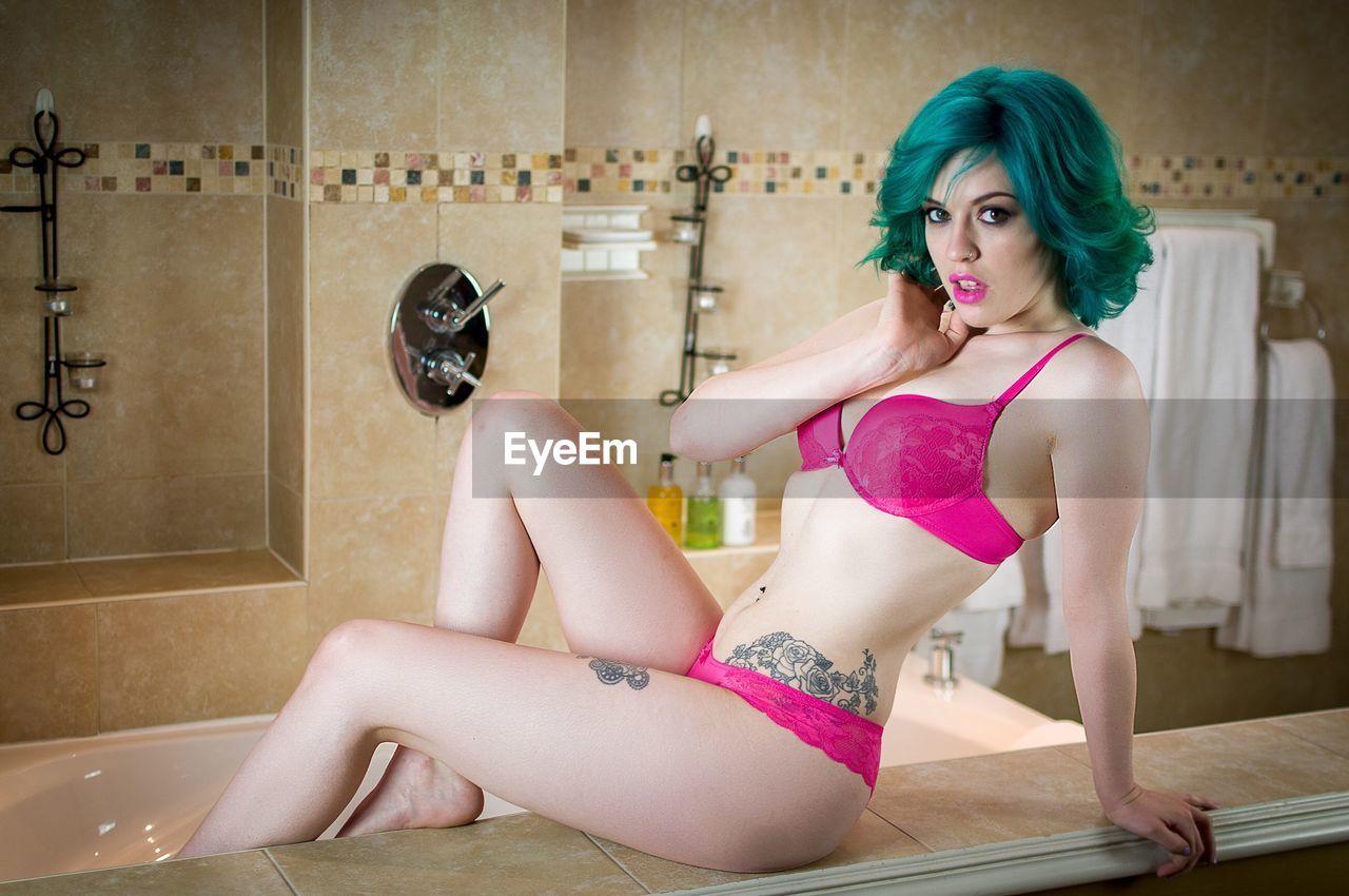 Portrait Of Young Woman In Bikini Sitting At Bathroom