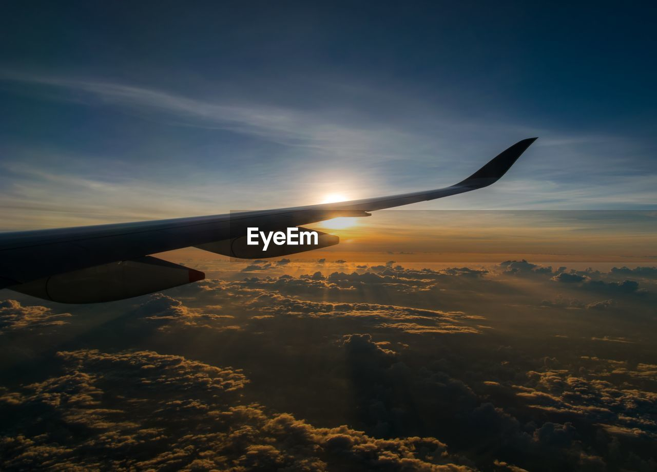 sky, air vehicle, cloud - sky, airplane, sunset, mode of transportation, transportation, aircraft wing, flying, beauty in nature, mid-air, scenics - nature, nature, public transportation, travel, sun, no people, orange color, outdoors, on the move, aerospace industry, plane
