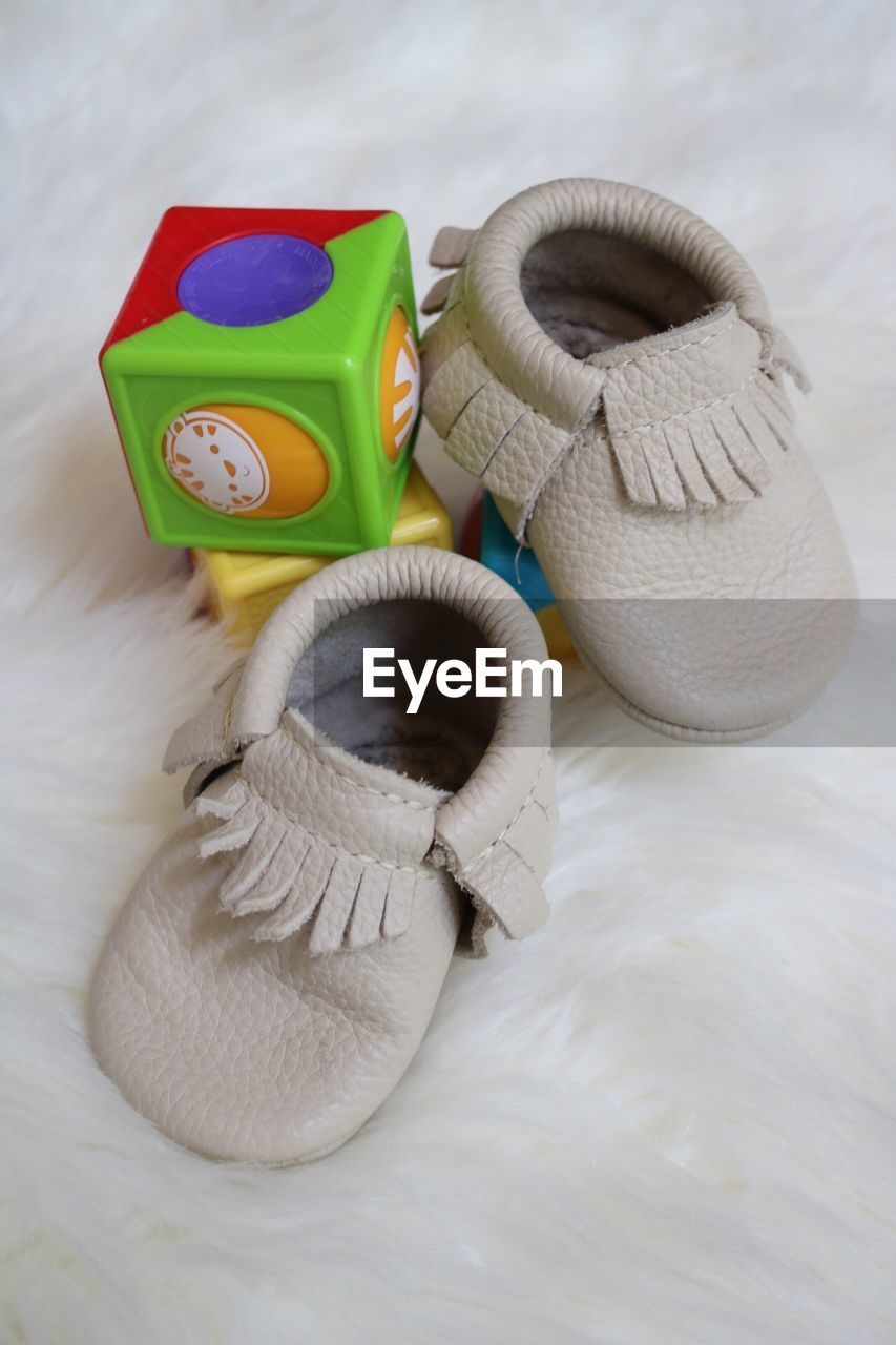 High angle view of baby booties and toys