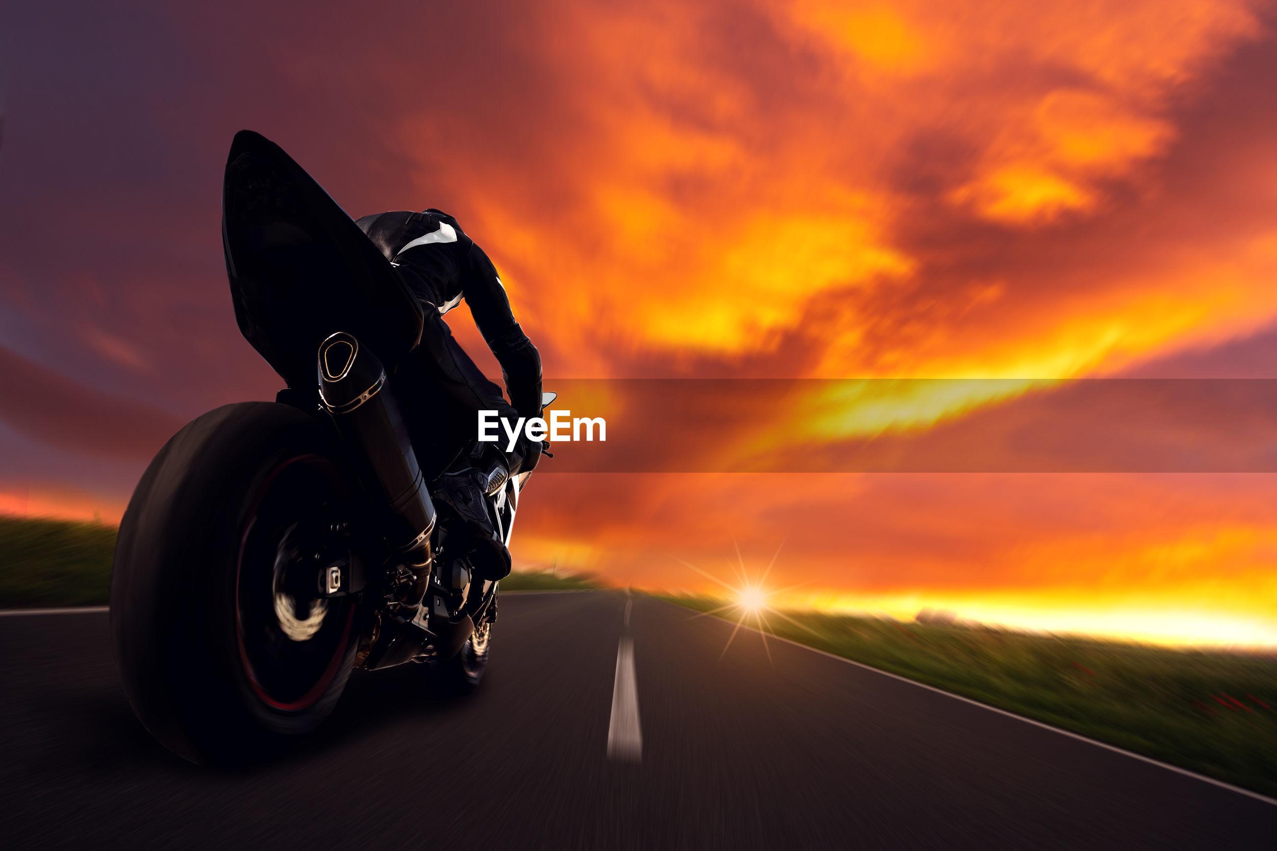 MOTORCYCLE ON ROAD AGAINST ORANGE SKY