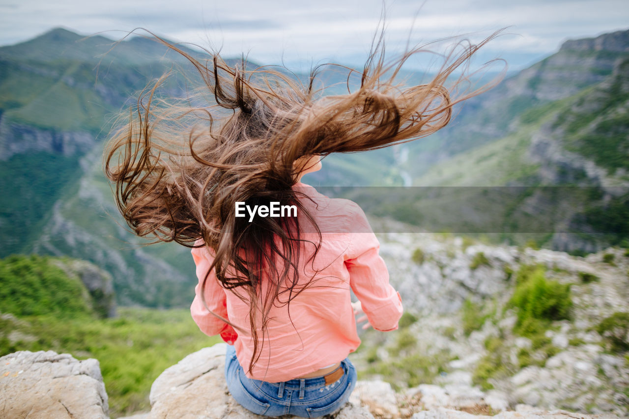 Young Woman Looking At Mountain Against Sky