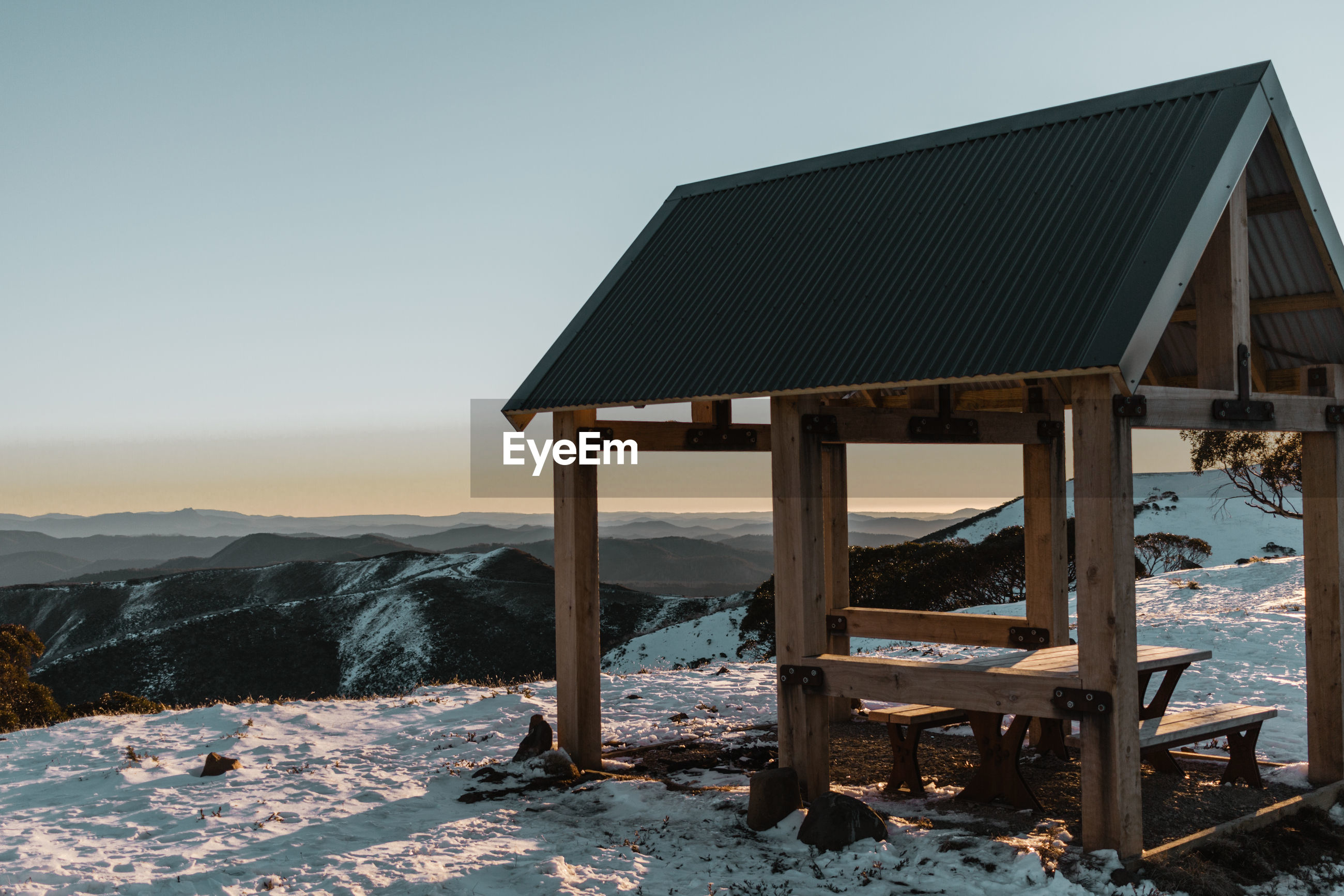 Gazebo on snow covered land against clear sky