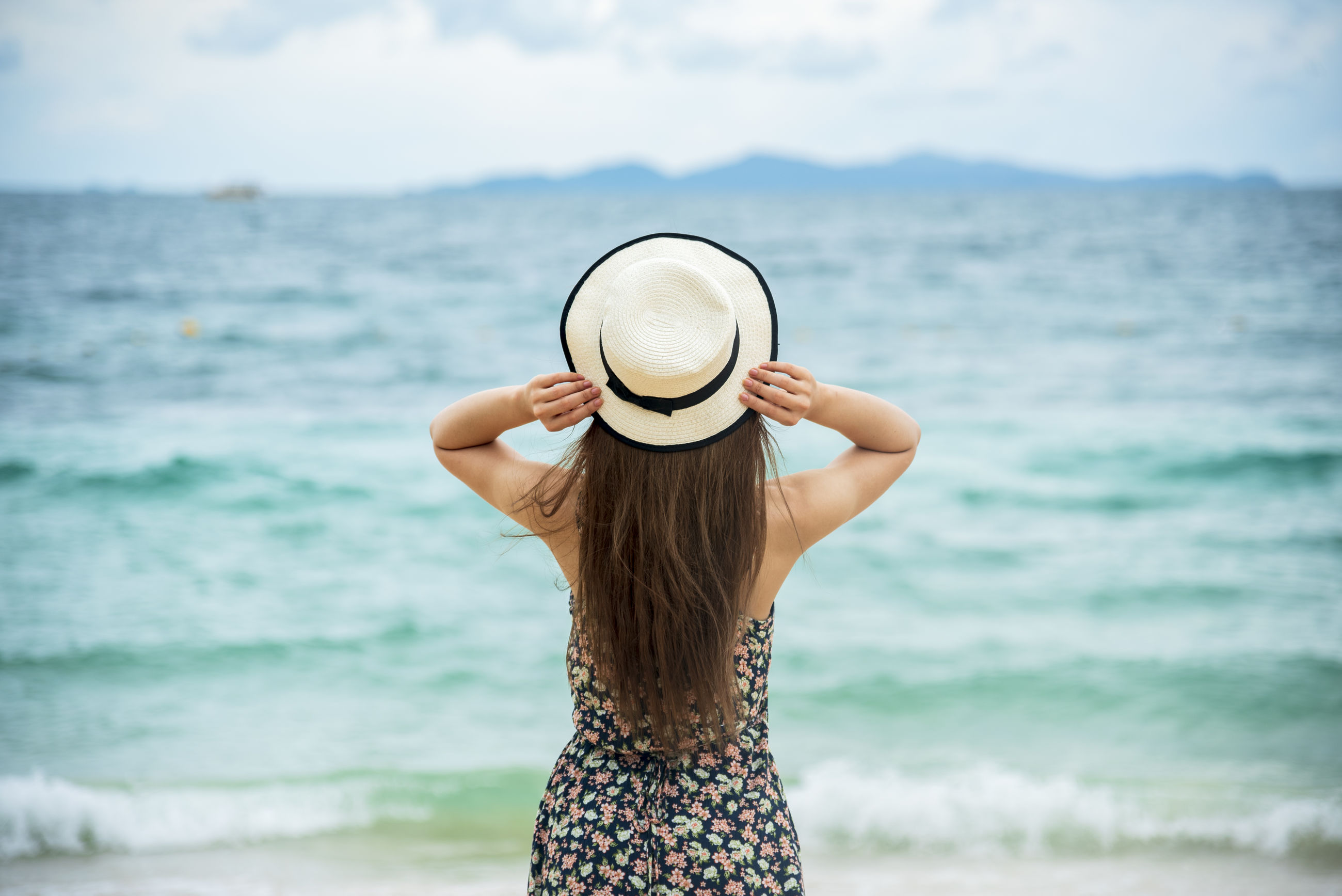 WOMAN HOLDING HAT STANDING AT BEACH