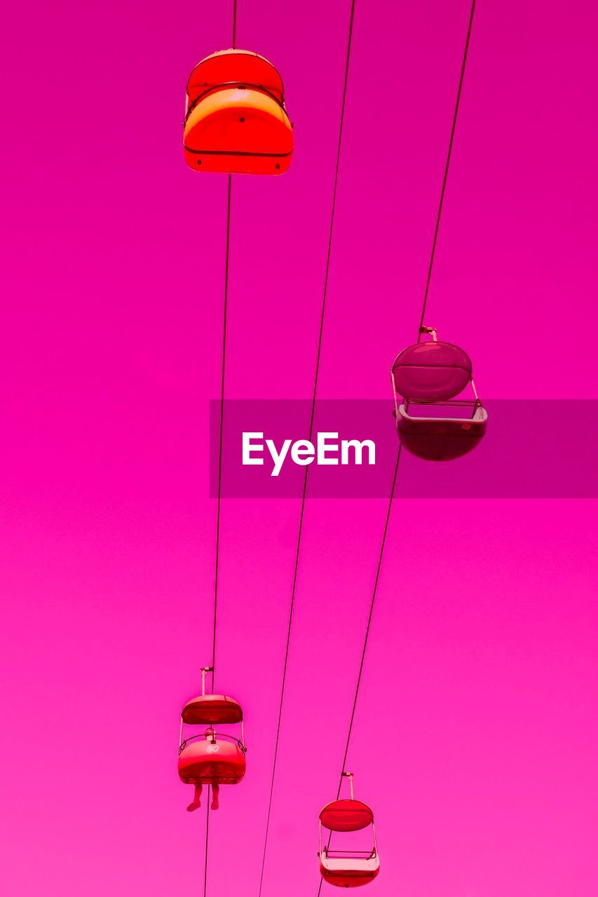 LOW ANGLE VIEW OF ILLUMINATED LIGHT BULBS HANGING ON PINK WALL