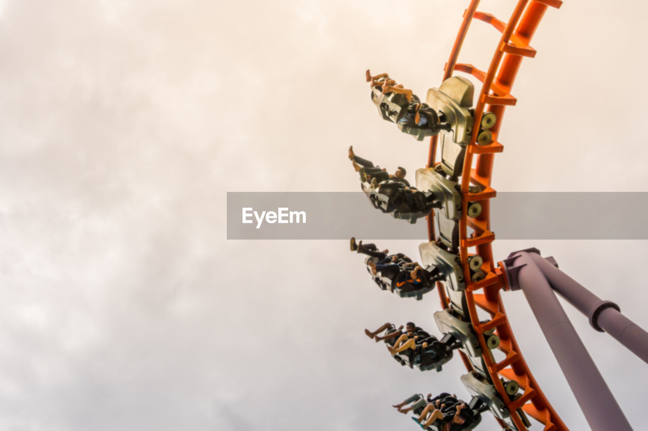Low Angle View Of People On Rollercoaster Against Sky