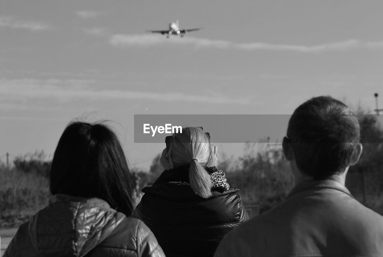 Rear View Of People Watching Flying Airplane Against Sky