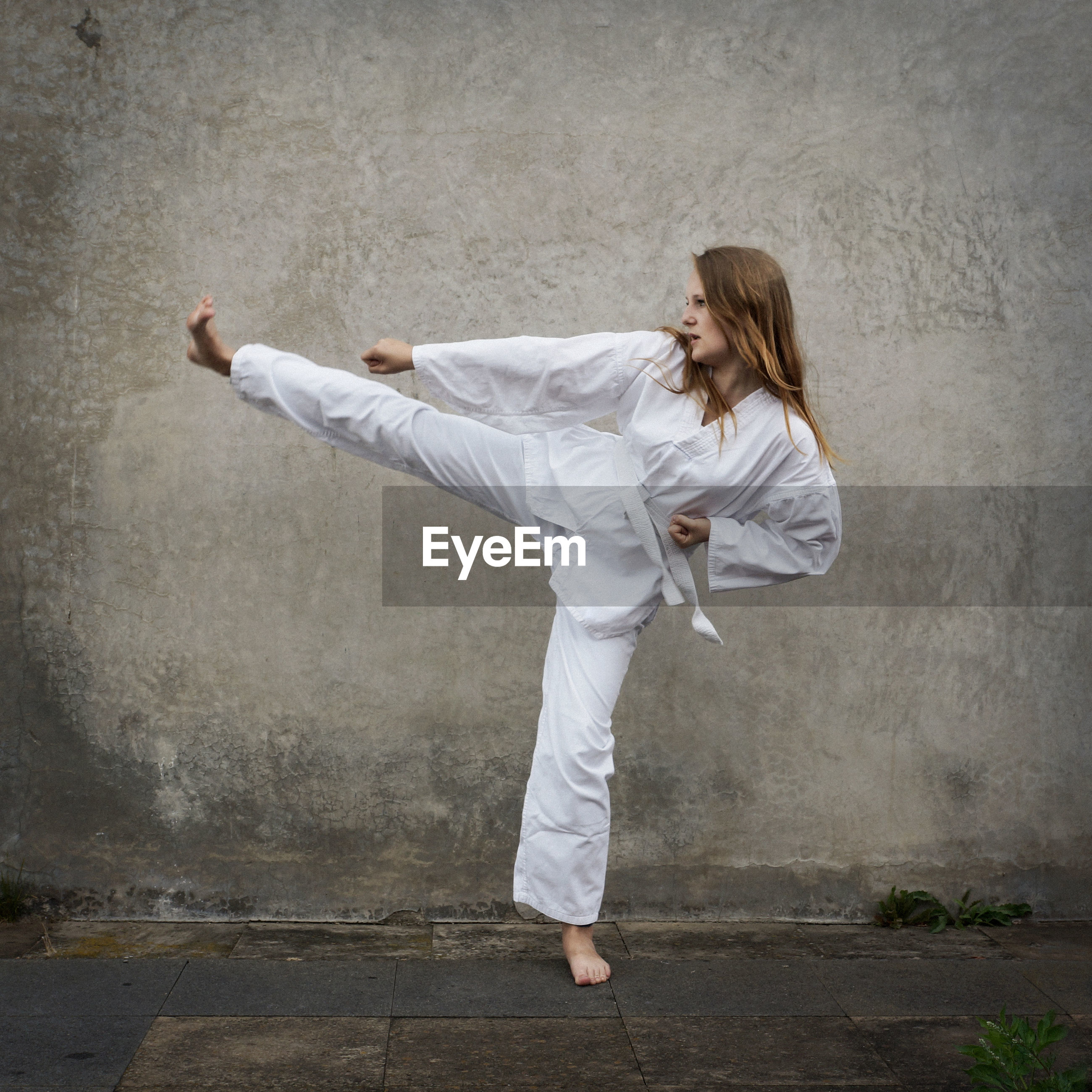 Young woman practicing karate against wall