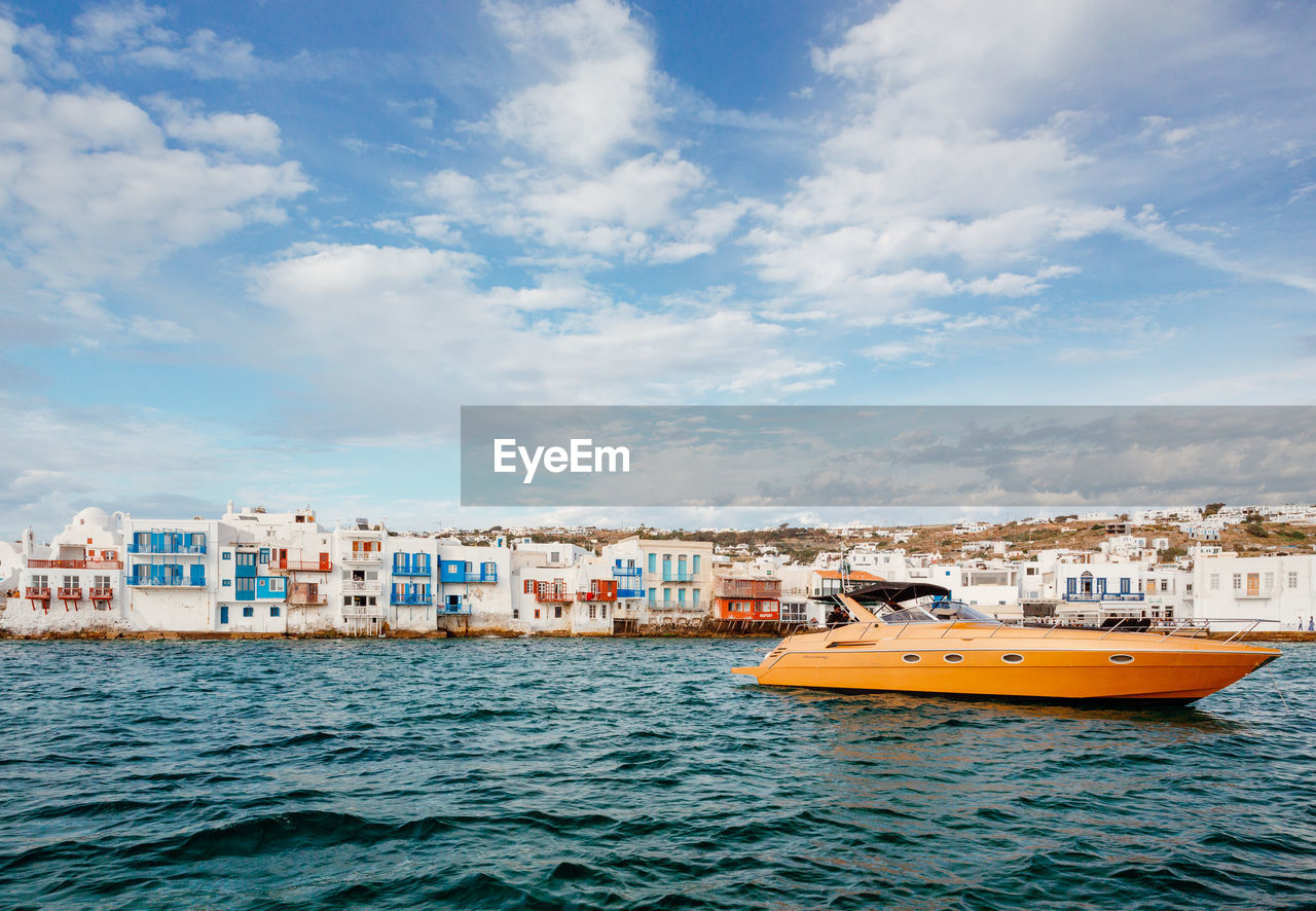 BOATS IN SEA BY BUILDINGS AGAINST SKY