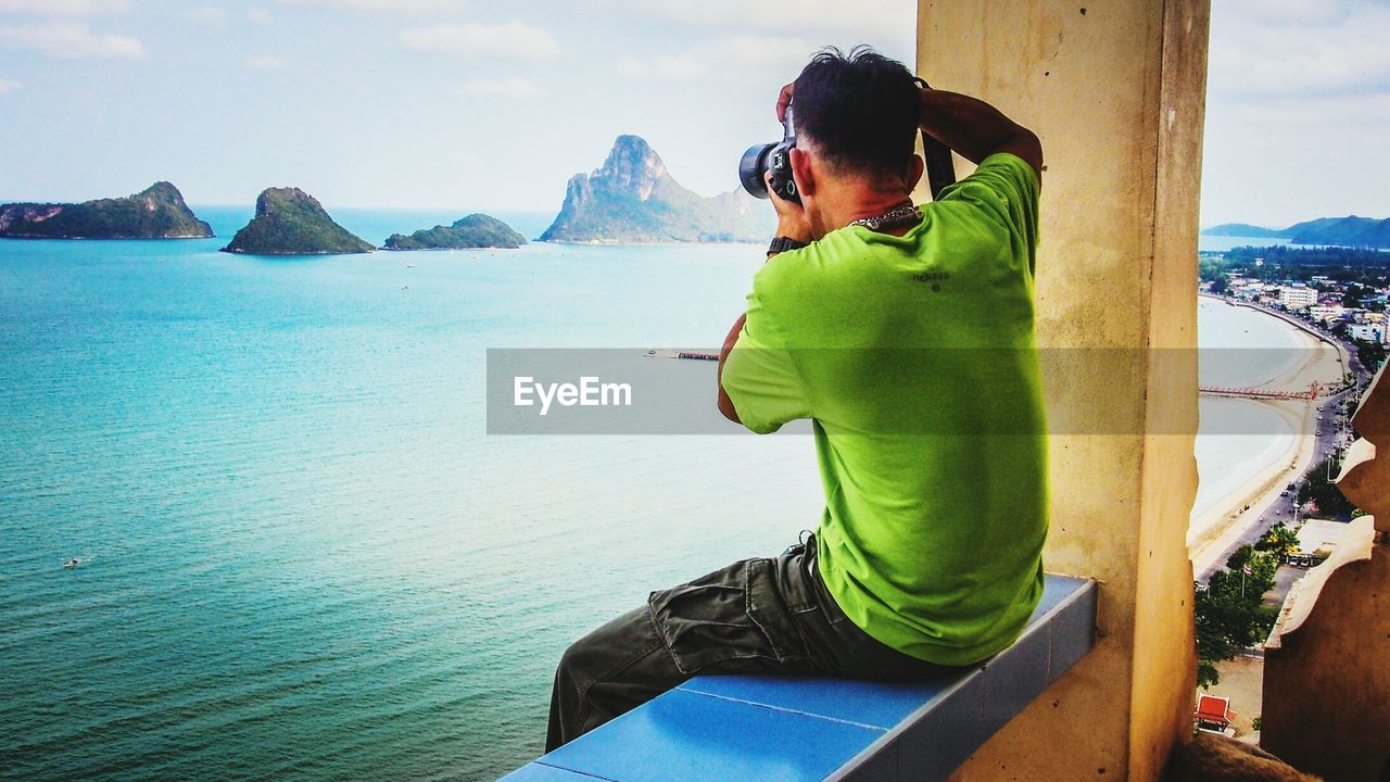 Rear View Of Man Photographing Mountains And Sea While Sitting On Retaining Wall