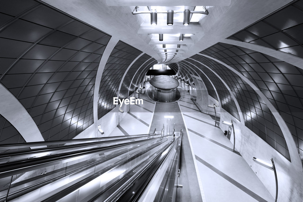 illuminated, architecture, indoors, transportation, subway station, built structure, lighting equipment, public transportation, ceiling, rail transportation, tunnel, the way forward, subway, no people, direction, railing, technology, escalator, diminishing perspective, modern, light, track, architectural column, moving walkway