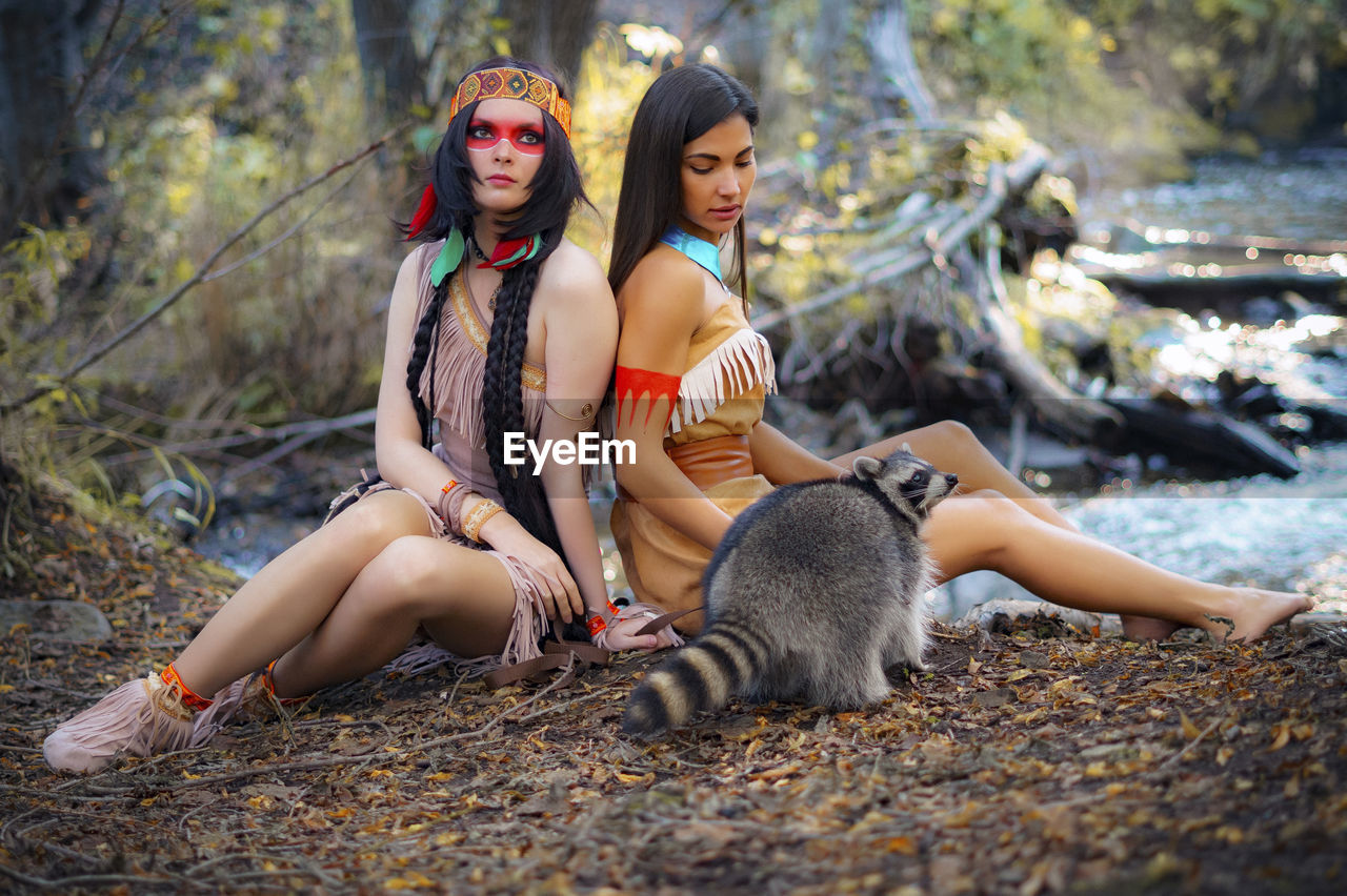 Young Women In Traditional Clothing Sitting By Raccoon In Forest