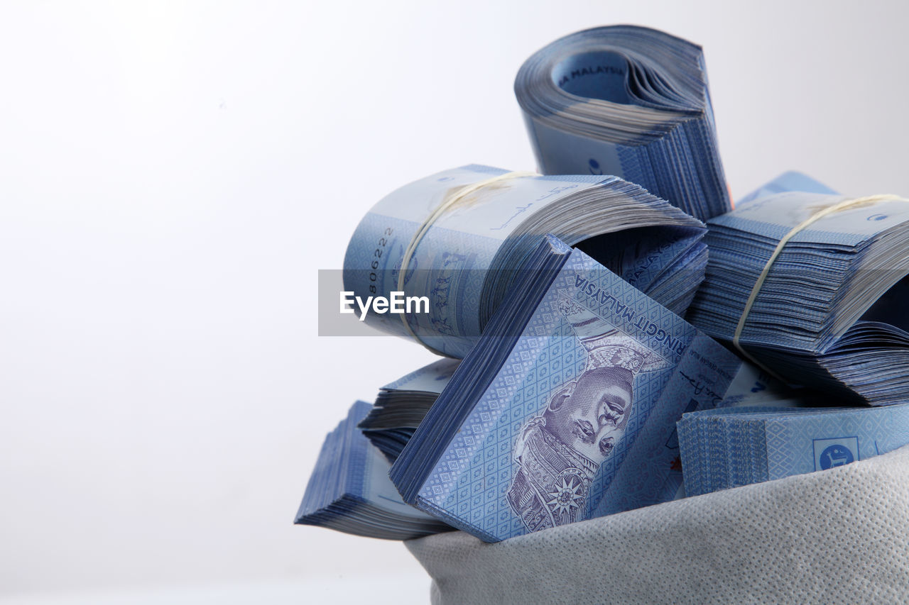 Close-Up Of Currencies In Sack Over White Background