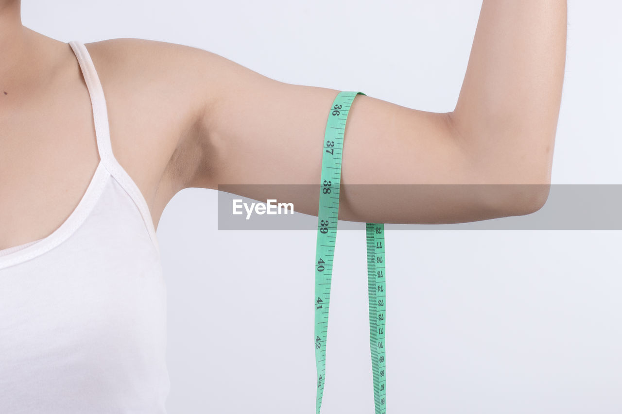 Cropped image of arm with measuring tape against white background