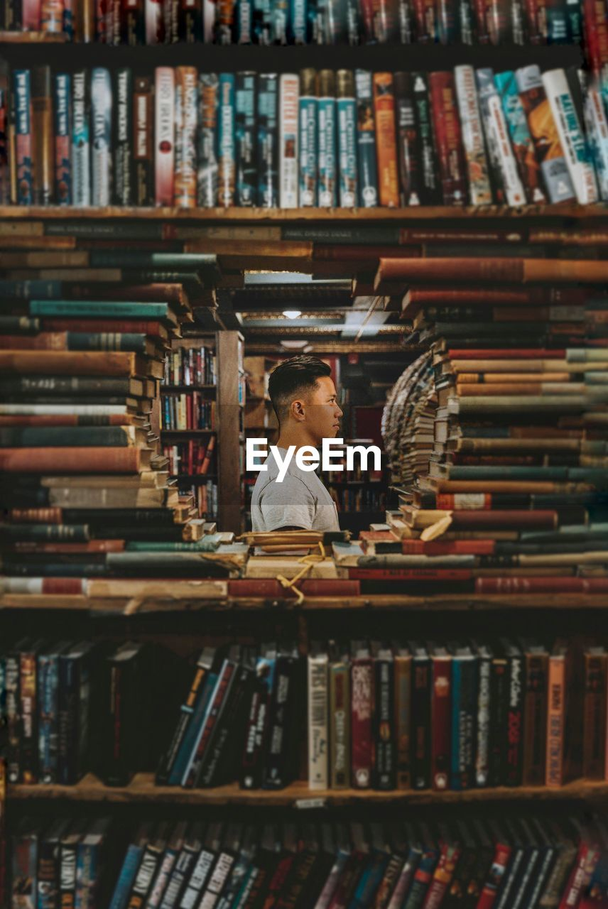 Man Standing Amidst Books In Library
