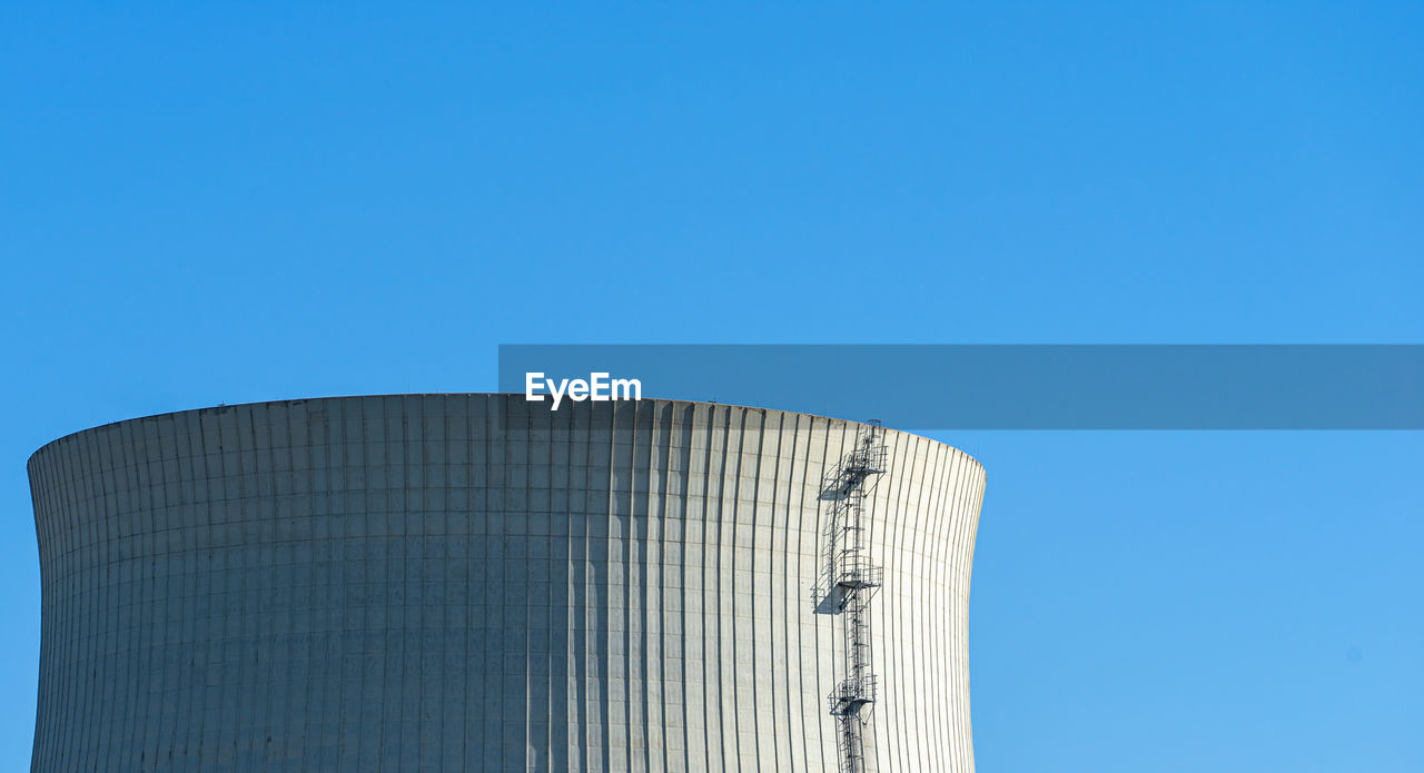 Low angle view of cooling tower against clear blue sky