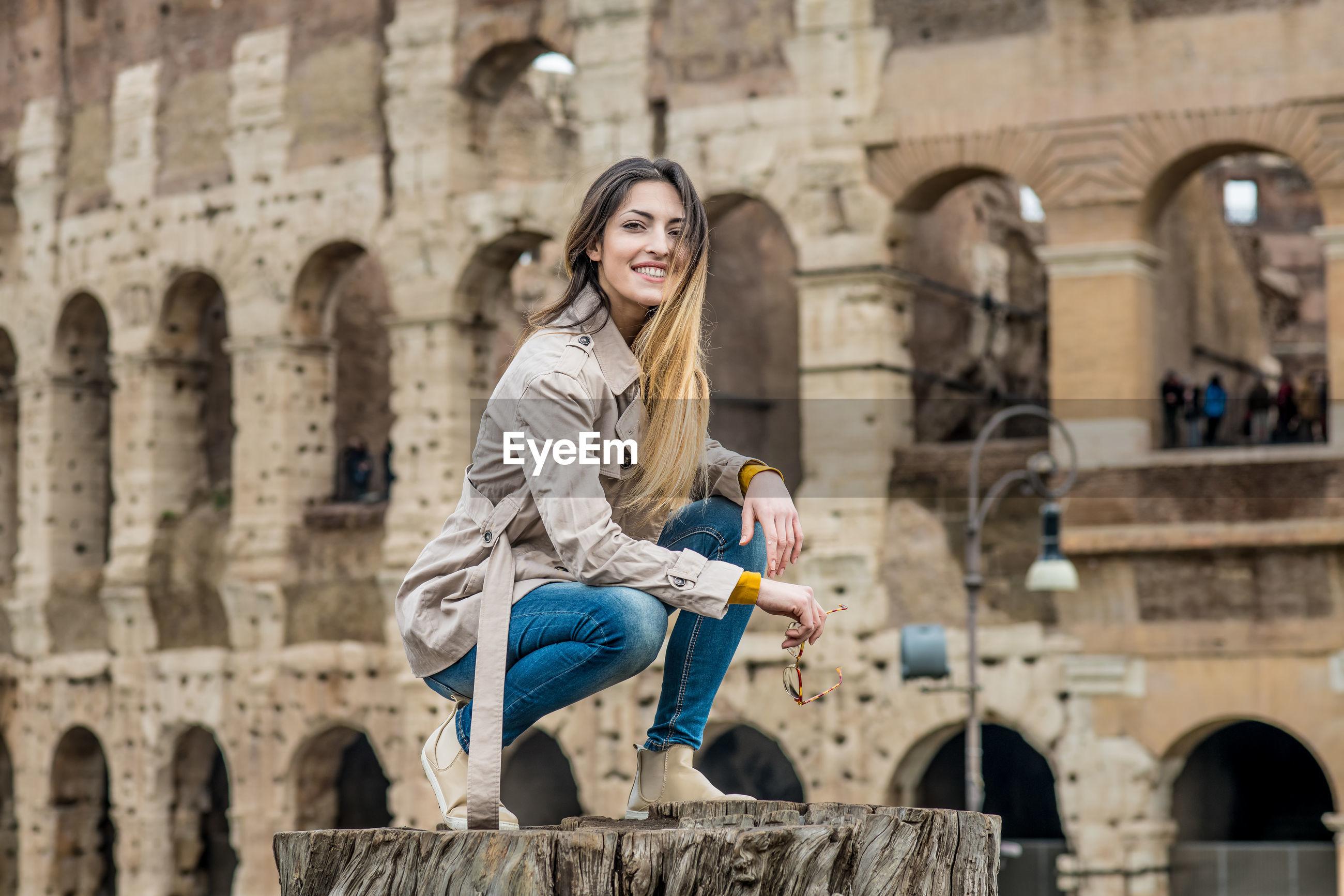 Portrait of young woman against coliseum