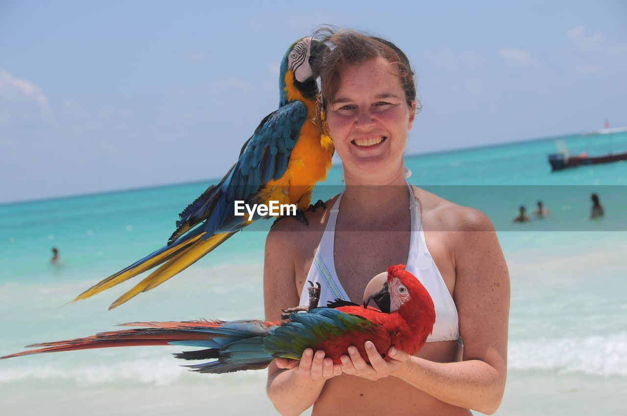 Portrait of smiling woman with parrots standing at beach