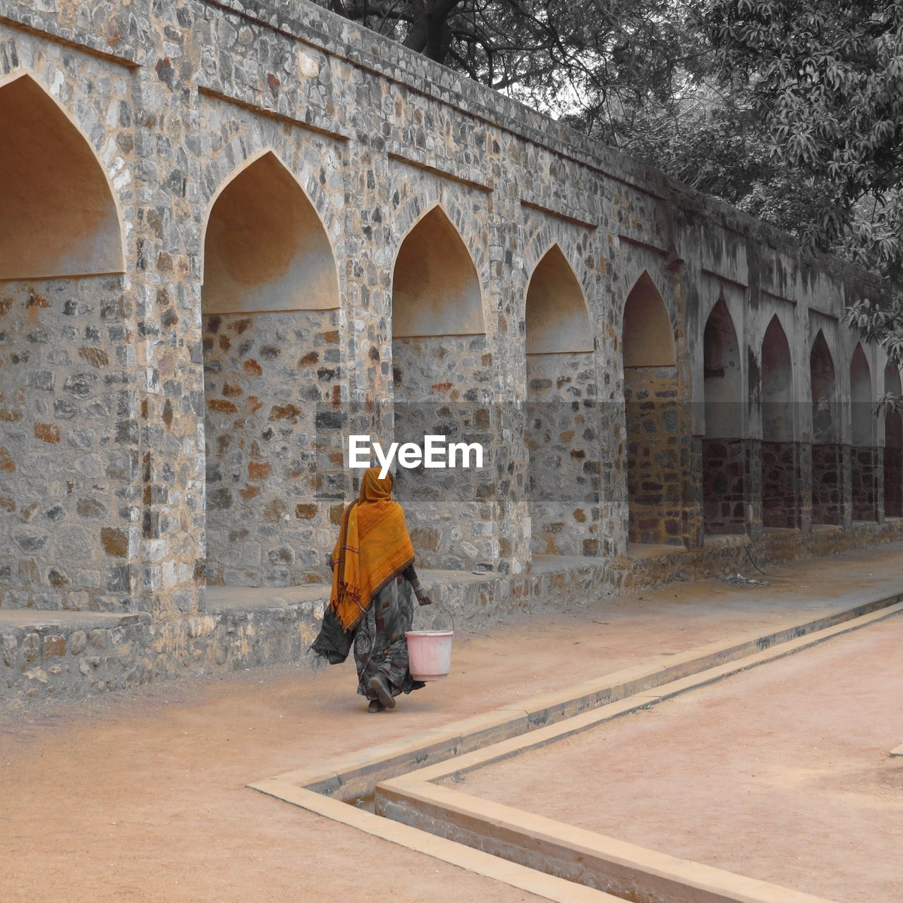 Rear view of a woman walking by arched structure