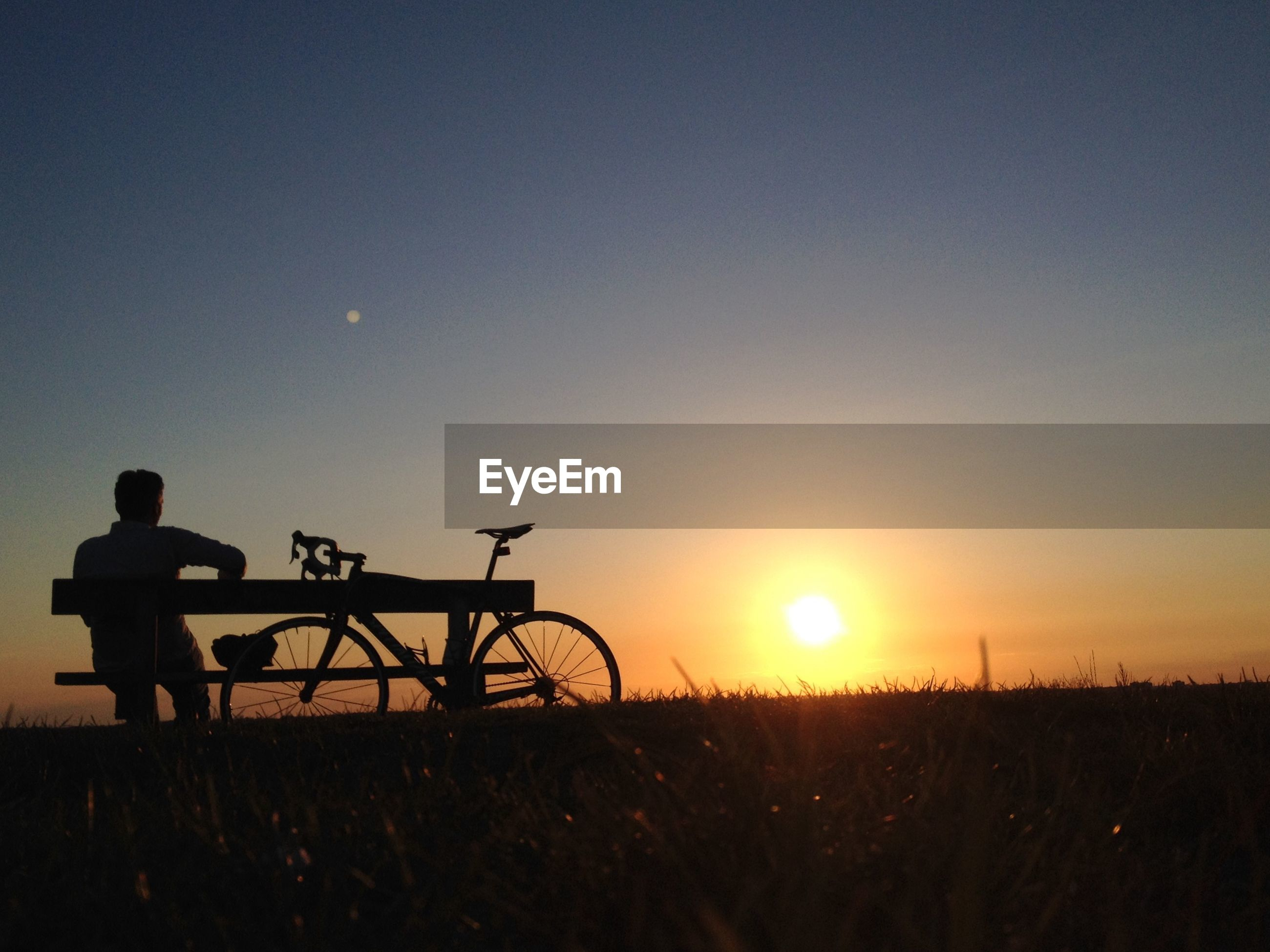 Rear view of man sitting on bench by bicycle at field against sky during sunset