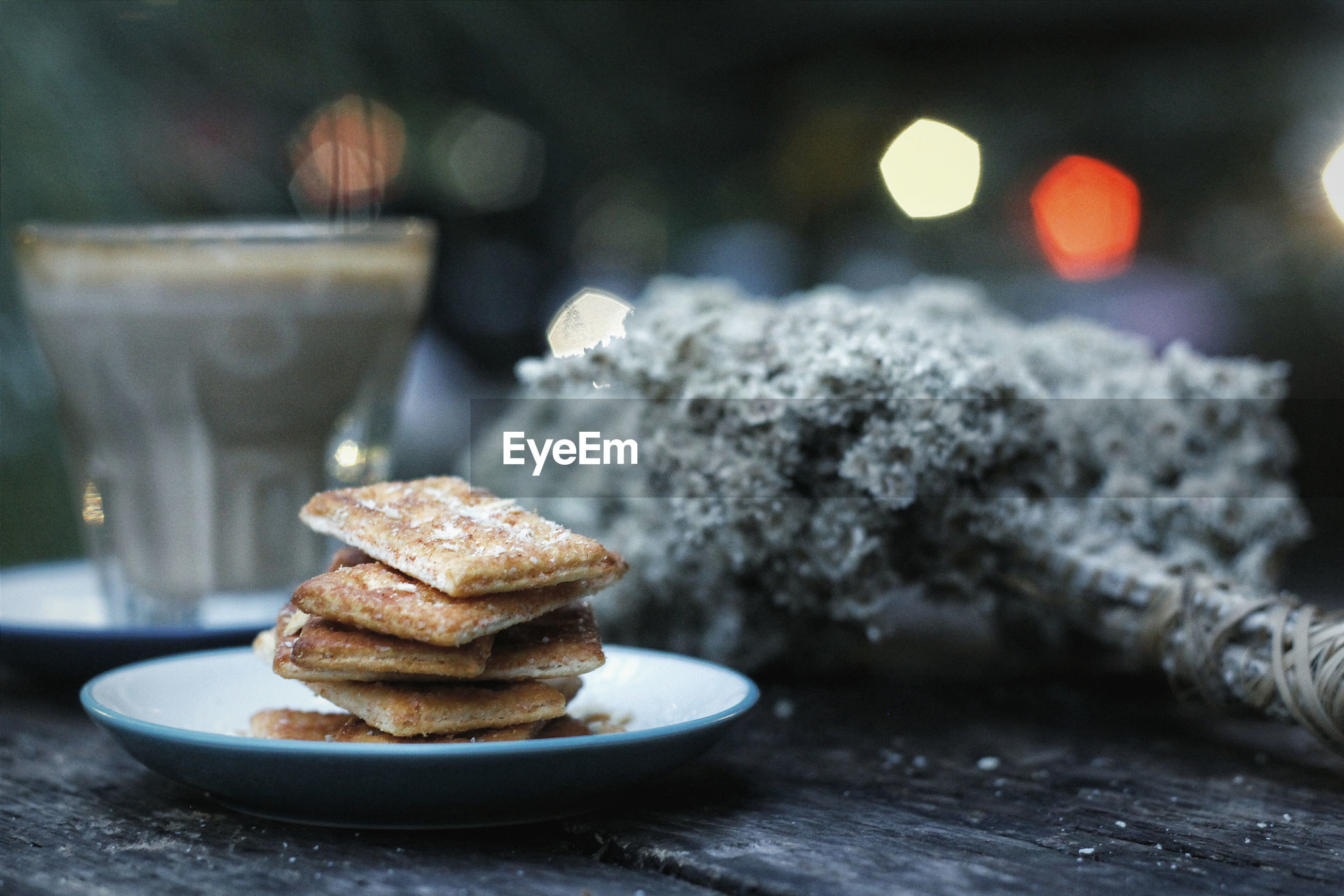 Stacked biscuits in plate by coffee on table