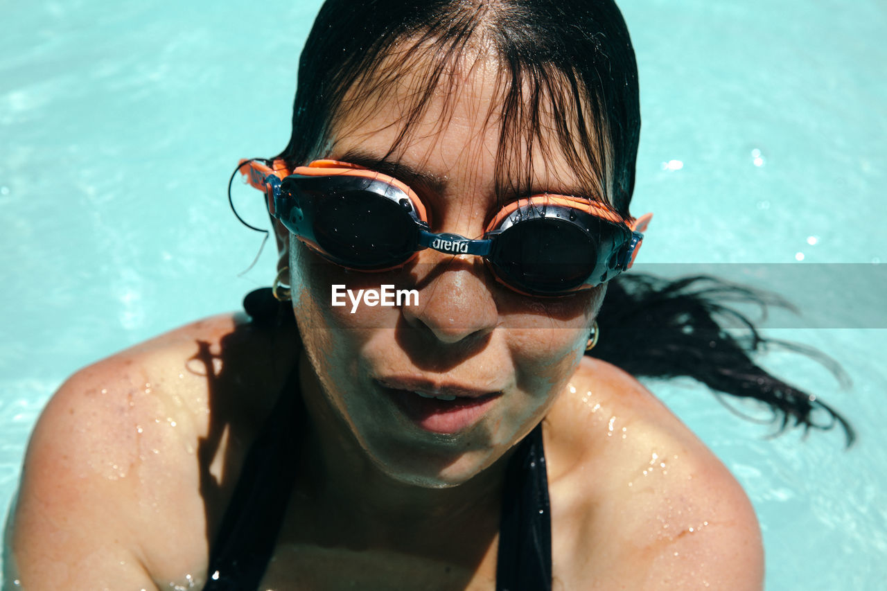 CLOSE-UP PORTRAIT OF YOUNG WOMAN WEARING SUNGLASSES SWIMMING POOL