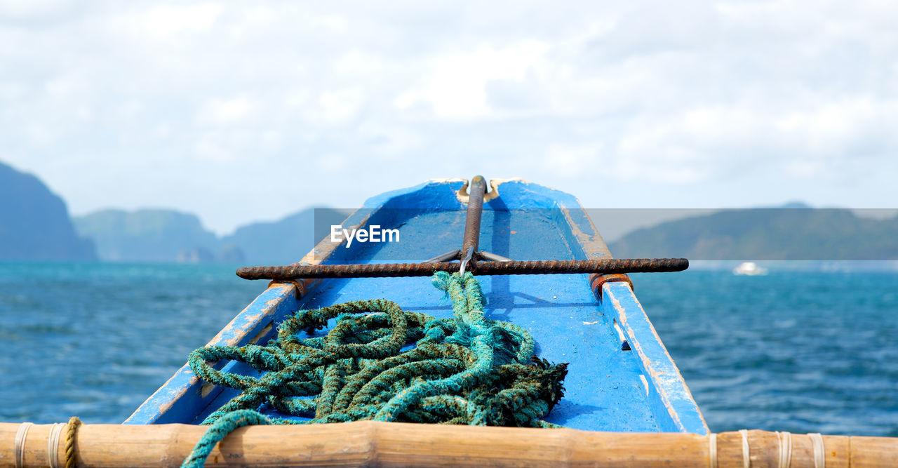 water, rope, sea, nautical vessel, transportation, day, sky, nature, no people, mode of transportation, cloud - sky, mountain, close-up, focus on foreground, tied up, strength, outdoors, blue, metal, turquoise colored
