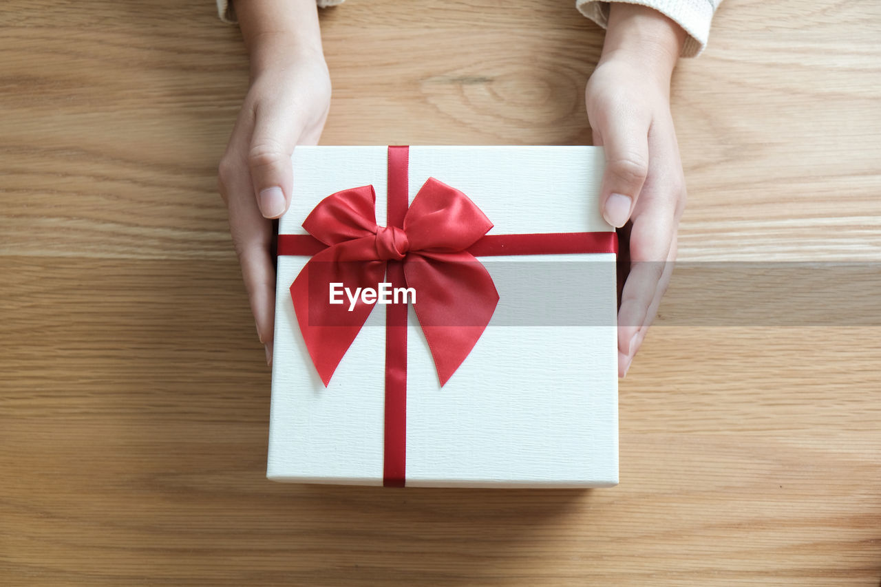 Cropped Hand Of Woman Holding Gift Box On Wooden Table