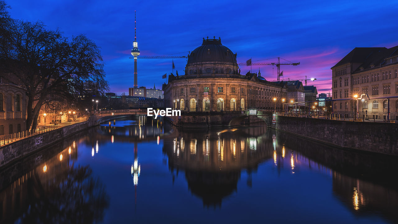 Illuminated Fernsehturm And Historic Building At Night