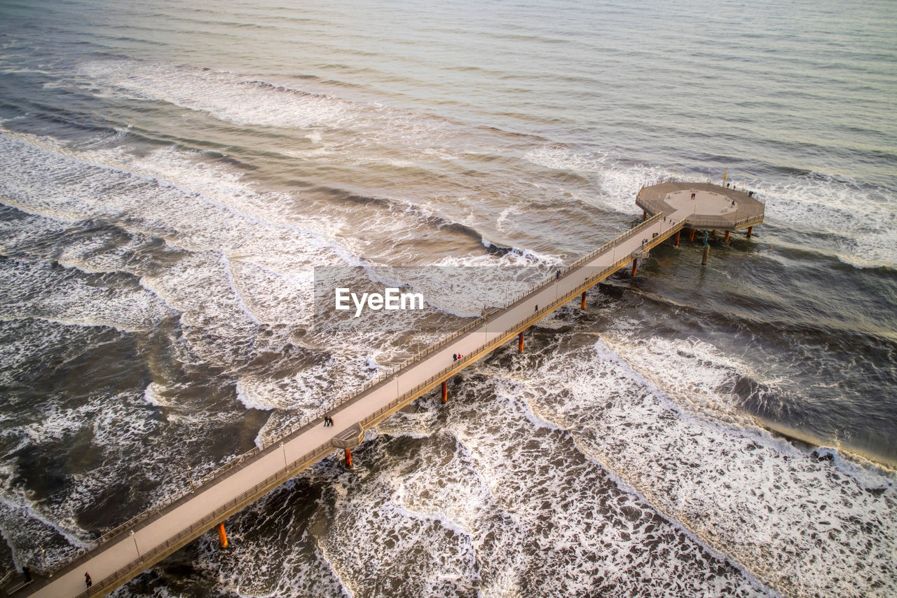 water, motion, sea, high angle view, nature, aquatic sport, day, no people, wave, sport, outdoors, flowing water, beach, land, beauty in nature, railing, scenics - nature, built structure, breaking, power in nature, flowing
