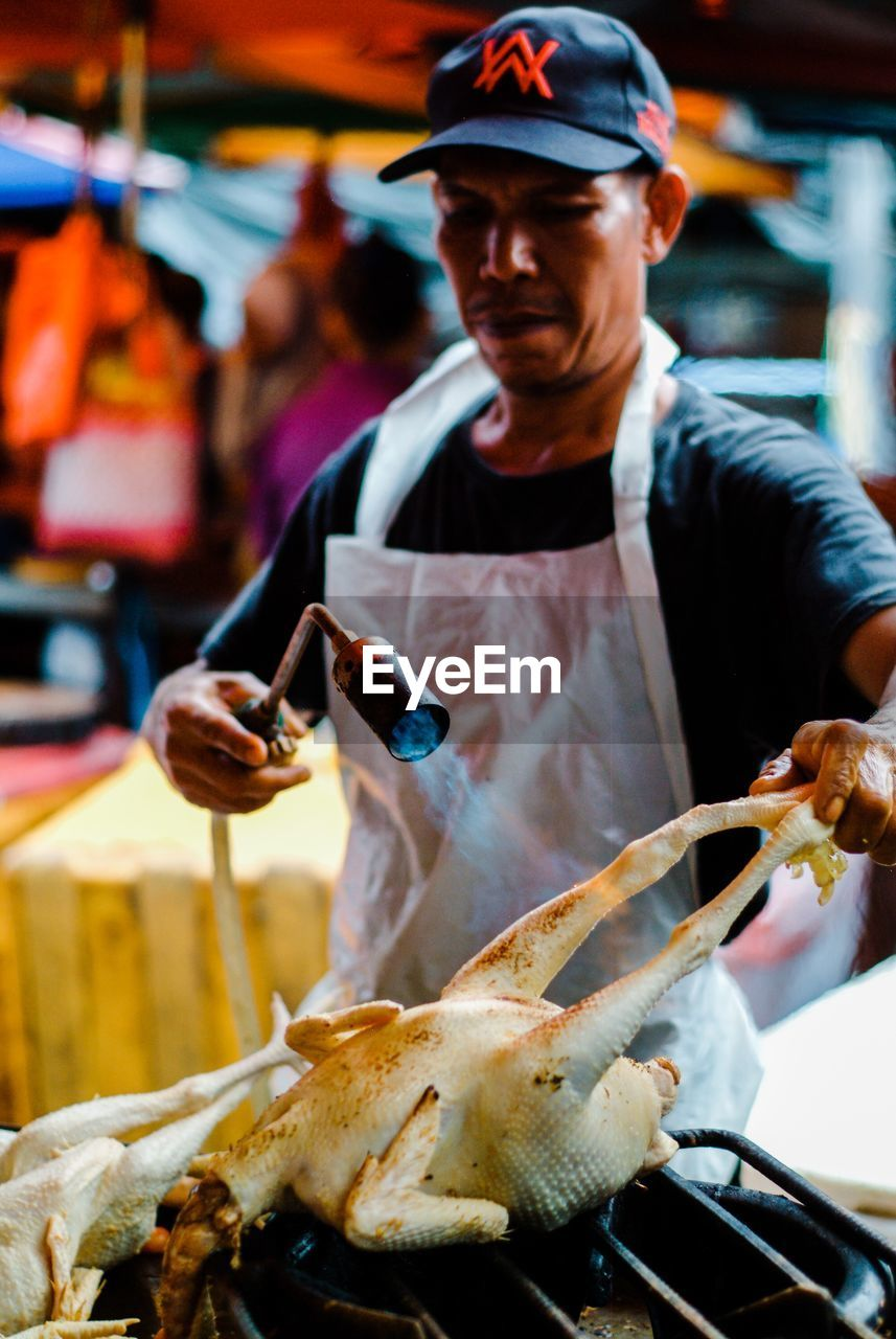 real people, one person, food, food and drink, front view, holding, occupation, business, freshness, incidental people, focus on foreground, fish, seafood, hat, waist up, men, preparation, retail, day, preparing food
