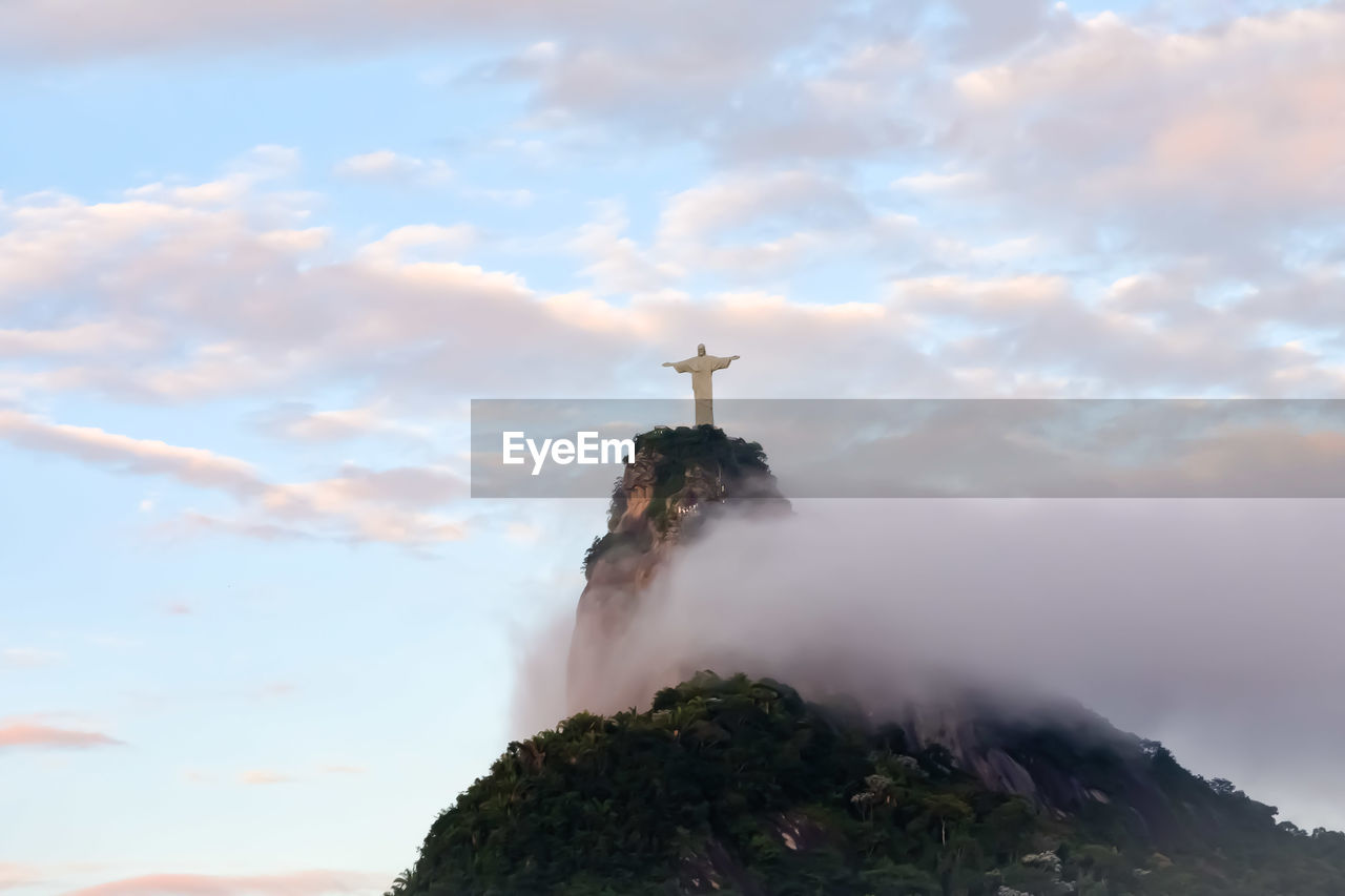 Low Angle View Of Jesus Christ Statue On Mountain Against Cloudy Sky