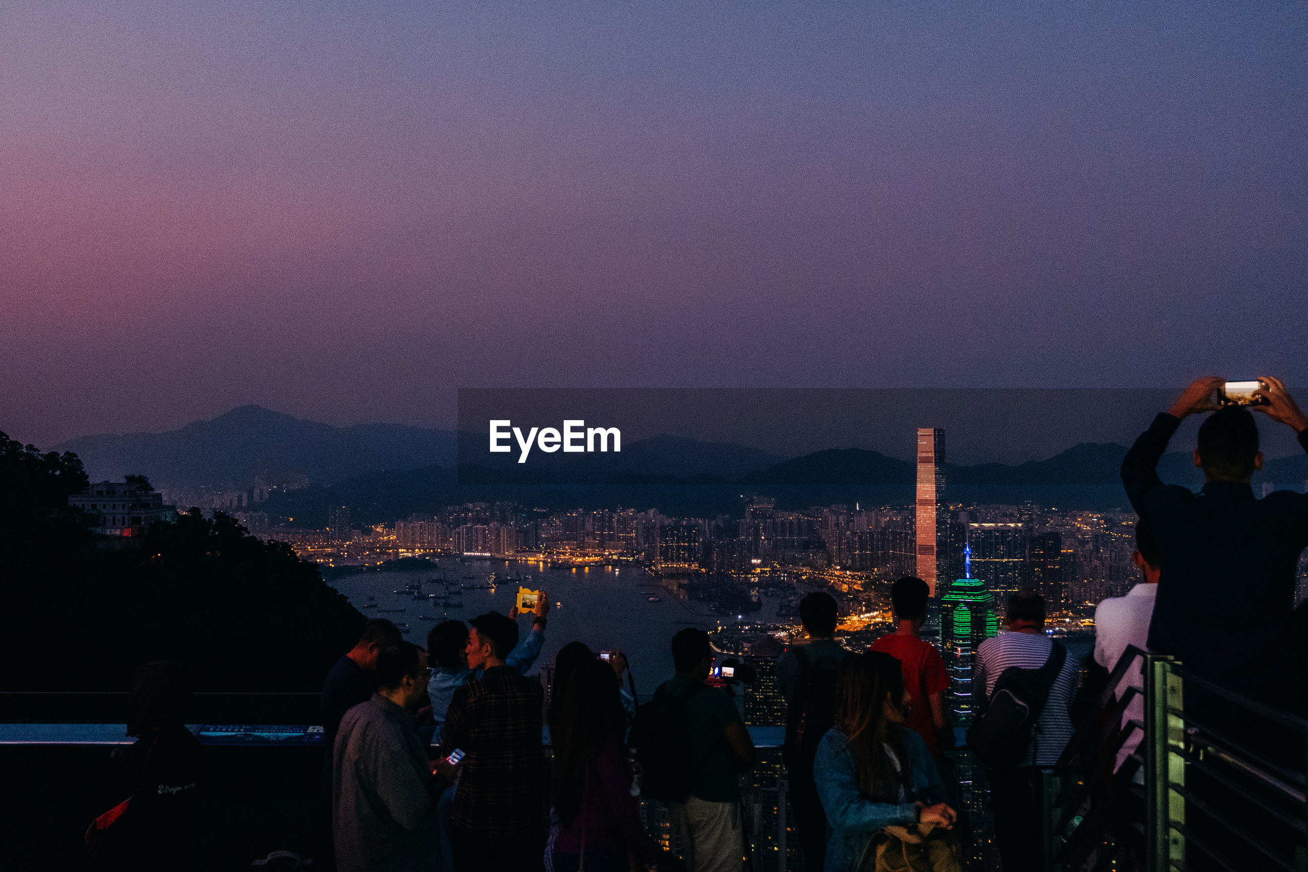 PEOPLE LOOKING AT ILLUMINATED CITYSCAPE AGAINST SKY