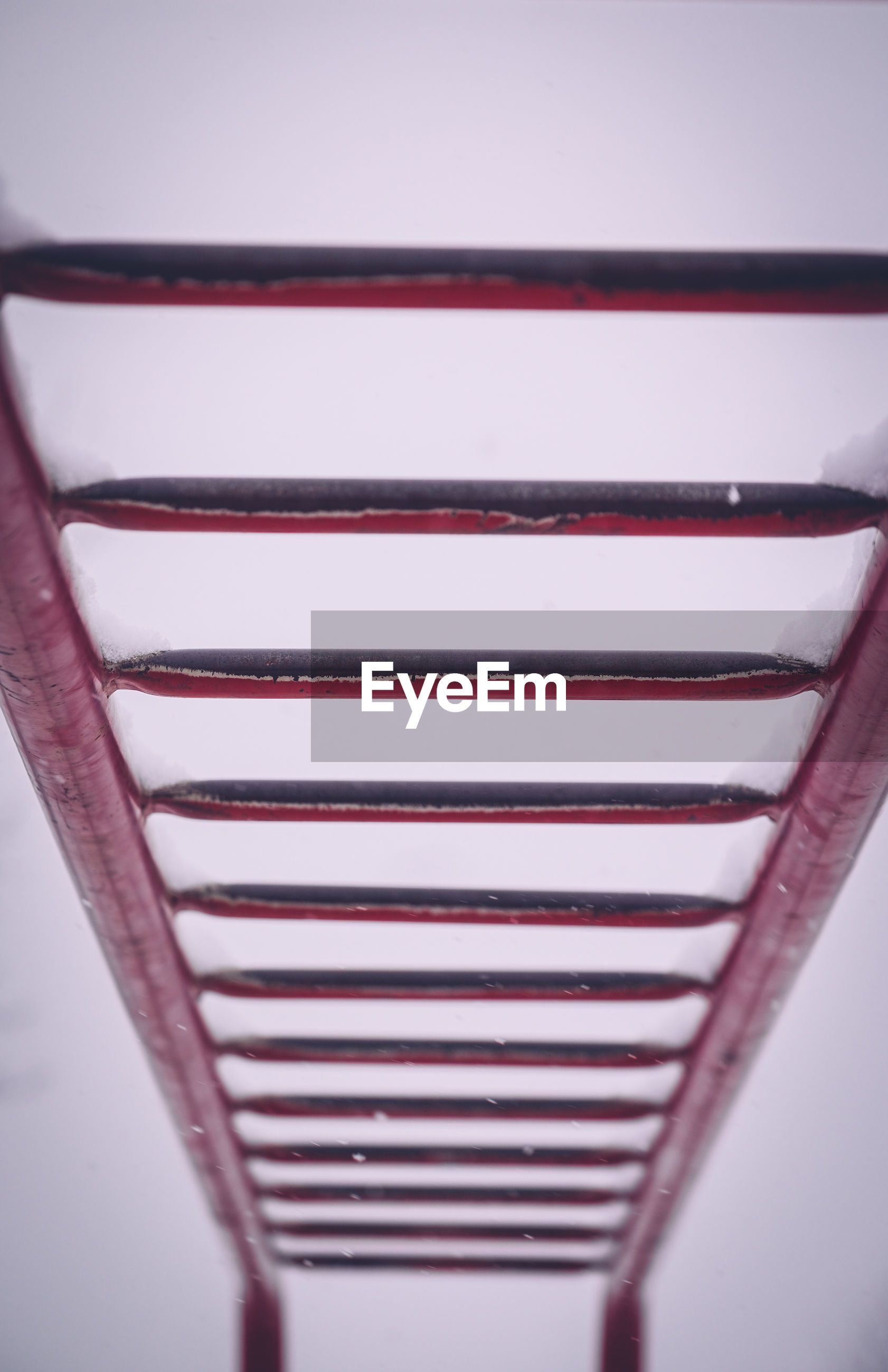 Low angle view of red metallic monkey bars against sky during winter