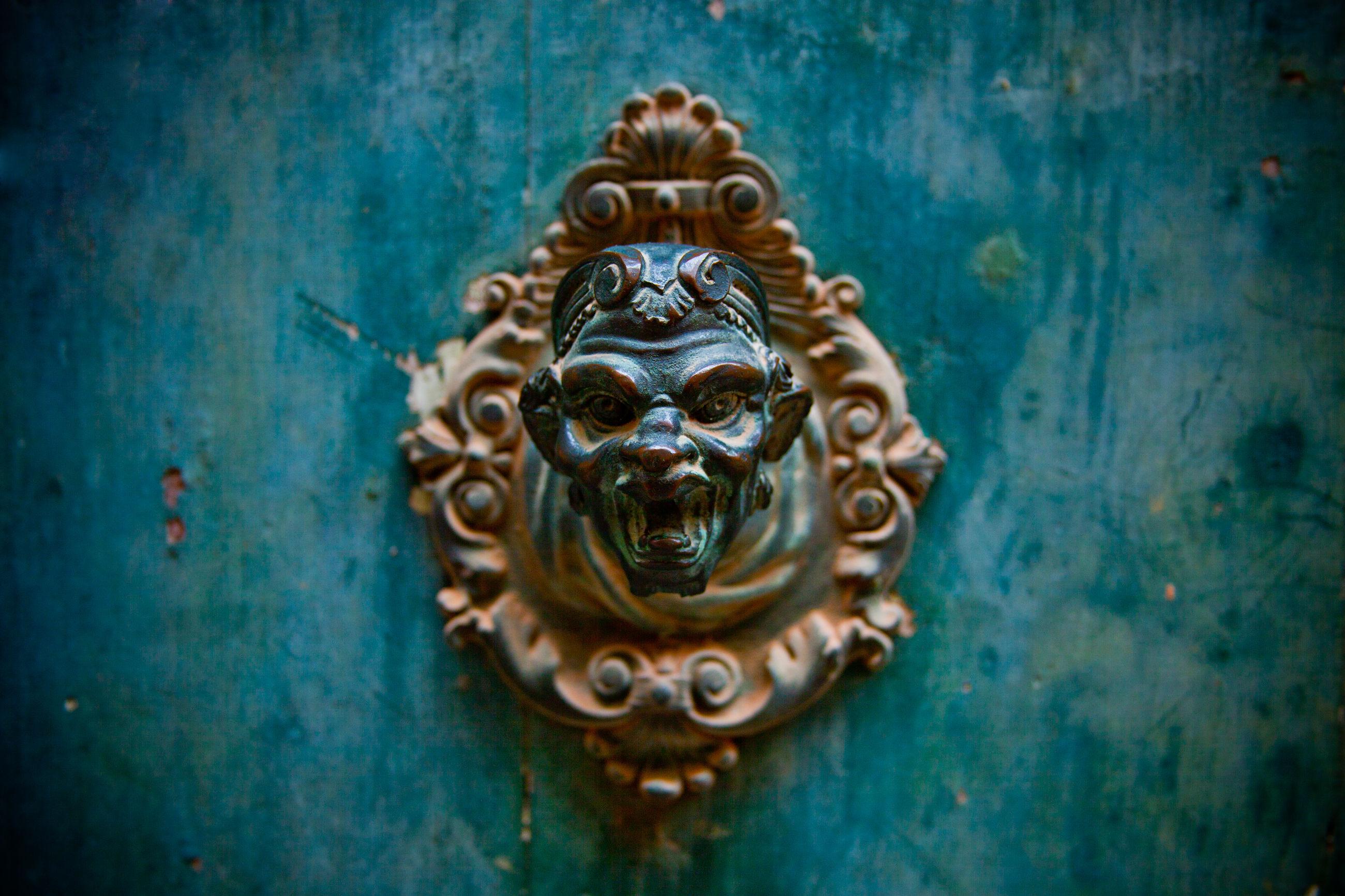 Close-up of vintage knocker on green door