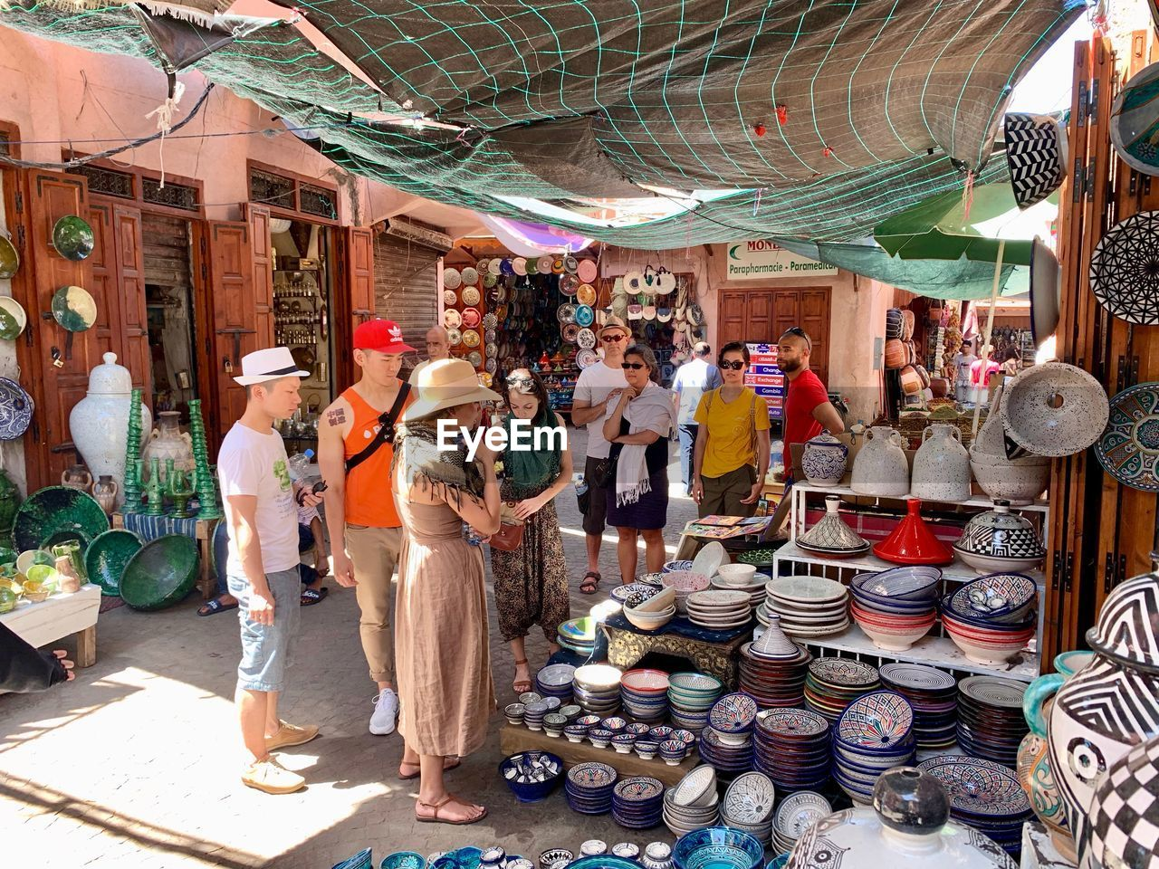 market, market stall, group of people, business, small business, men, retail, for sale, adult, choice, real people, shopping, women, day, retail display, large group of objects, people, variation, selling, street market, buying, sale, consumerism, outdoors