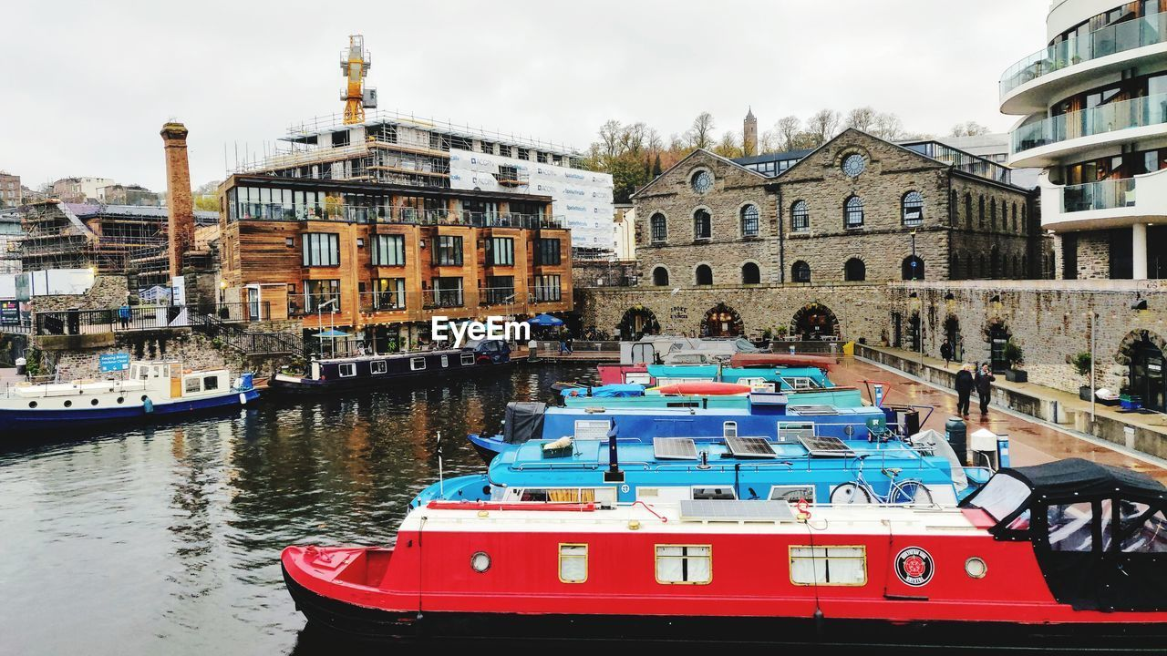 nautical vessel, transportation, mode of transportation, building exterior, water, built structure, architecture, city, day, moored, travel, nature, canal, sky, incidental people, group of people, travel destinations, building, tourism, outdoors, passenger craft