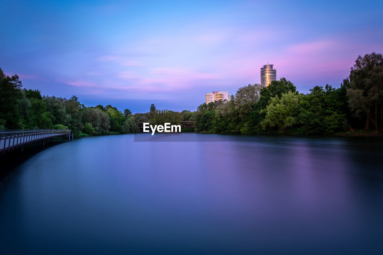 built structure, sky, architecture, water, waterfront, building exterior, tree, scenics - nature, nature, river, no people, plant, cloud - sky, beauty in nature, sunset, city, reflection, connection, outdoors, skyscraper, office building exterior