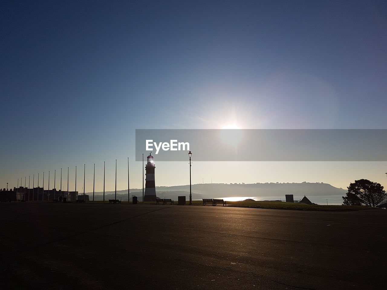 sky, sun, nature, architecture, sunlight, building exterior, built structure, sunset, tower, copy space, no people, scenics - nature, city, street, water, outdoors, sea, clear sky, beauty in nature, lighthouse, lens flare
