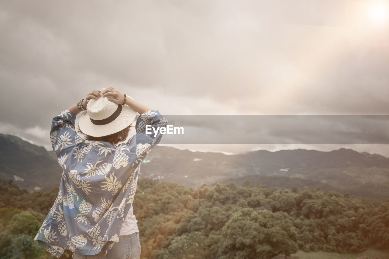 mountain, cloud - sky, sky, one person, scenics - nature, nature, beauty in nature, leisure activity, lifestyles, day, standing, clothing, tranquil scene, tranquility, non-urban scene, hat, real people, mountain range, three quarter length, outdoors, looking at view