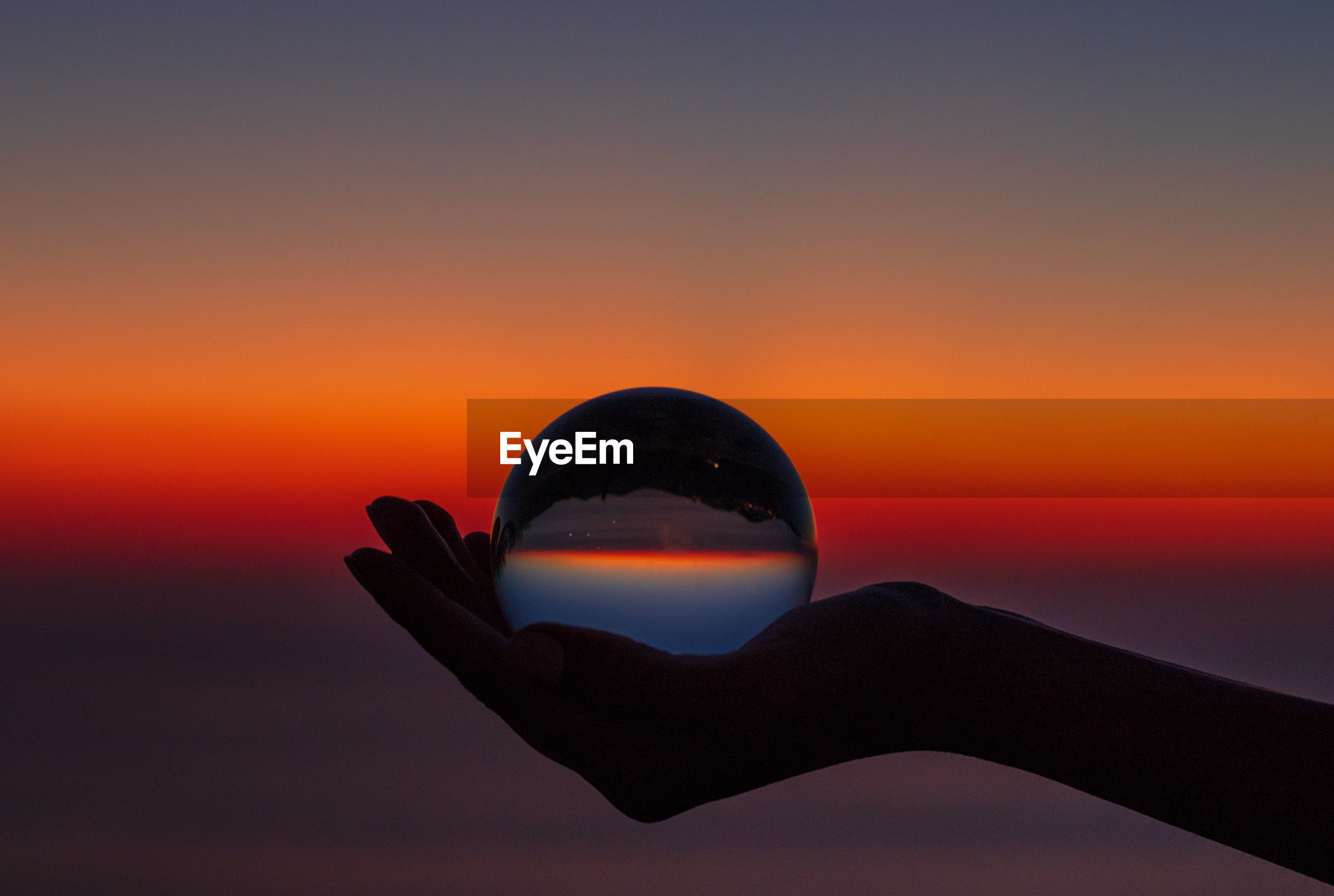 Cropped hand holding crystal ball against sky during sunset