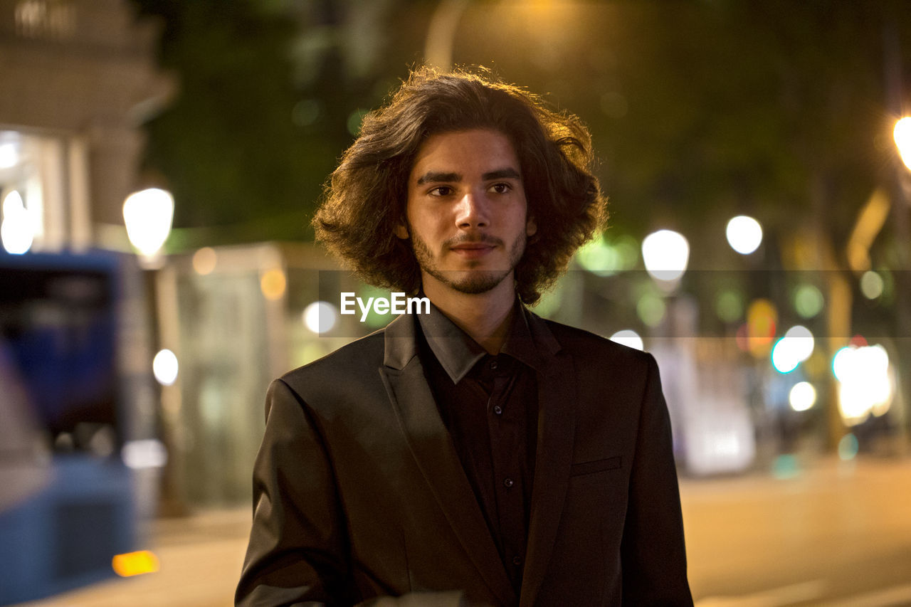 Portrait Of Young Man In Illuminated City At Night