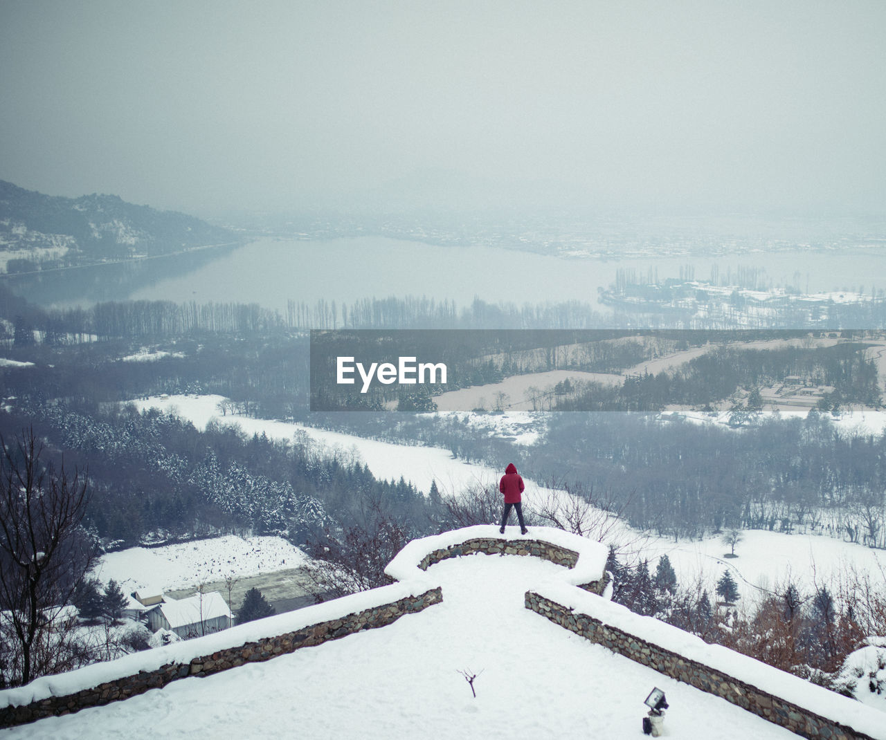 Rear view of person standing on railing against sky during winter