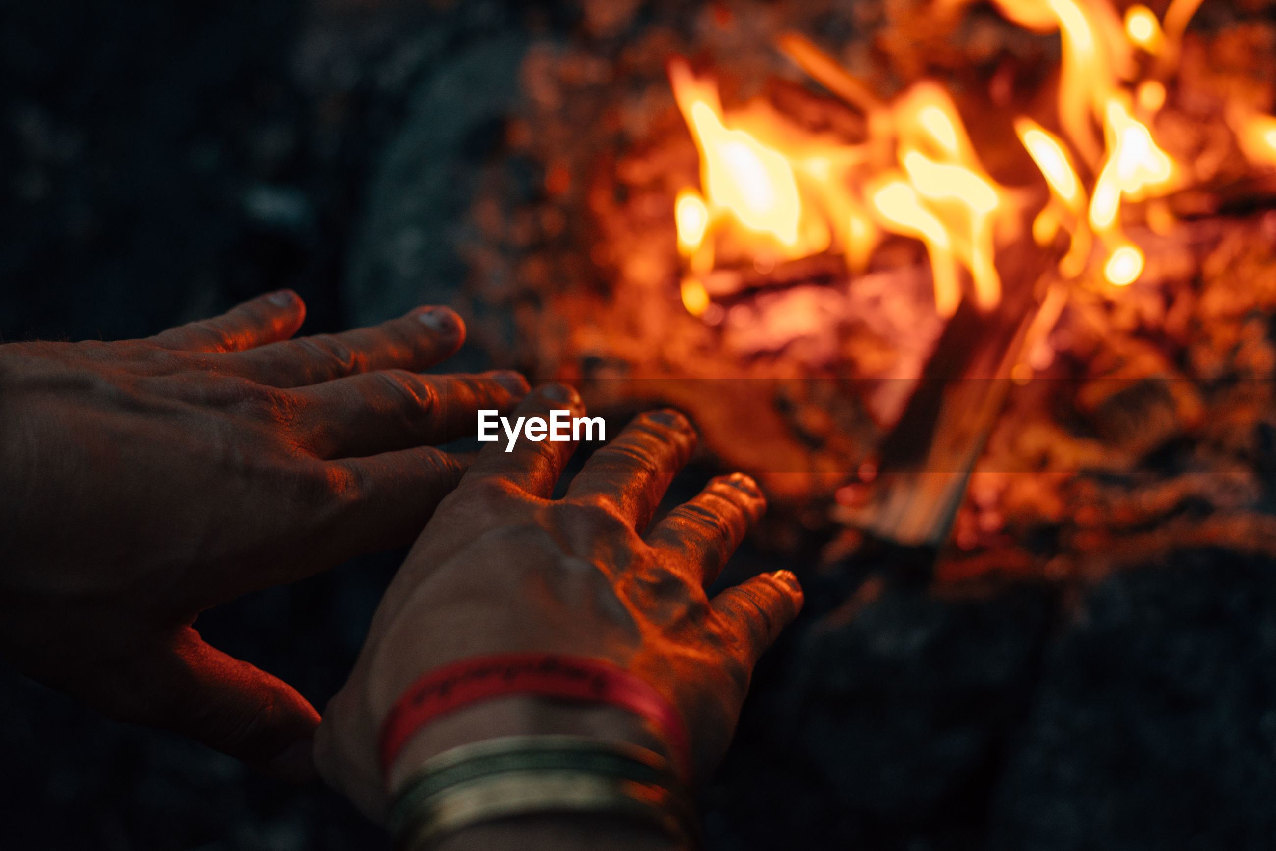 Cropped hands of person by bonfire at night