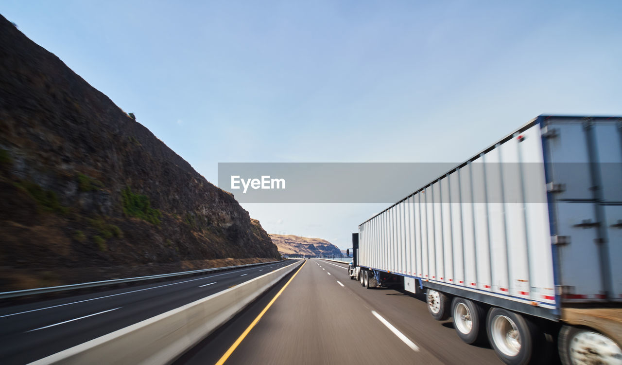 transportation, mode of transportation, land vehicle, road, sky, truck, motor vehicle, the way forward, motion, diminishing perspective, direction, nature, on the move, symbol, day, semi-truck, road marking, marking, no people, outdoors