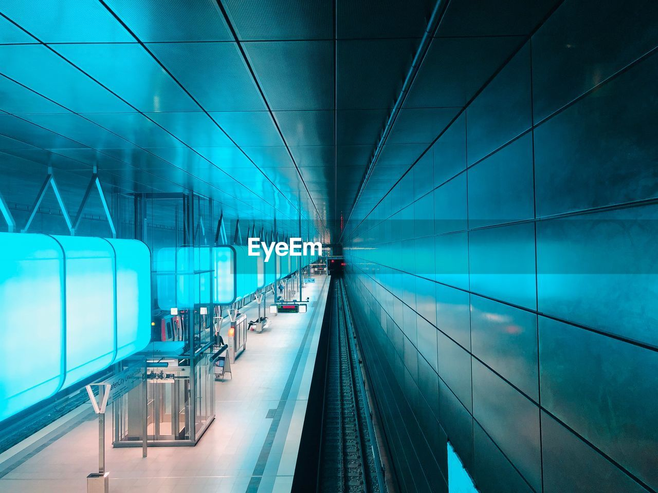 transportation, illuminated, architecture, mode of transportation, indoors, glass - material, rail transportation, public transportation, motion, built structure, subway station, modern, the way forward, incidental people, direction, travel, railroad track, track, ceiling, moving walkway, station, light