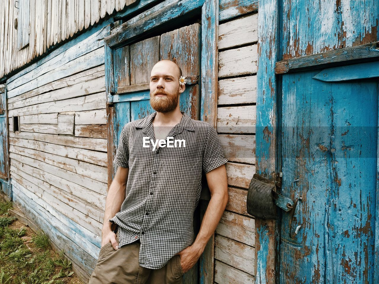 Bearded young man looking away while standing by wooden house