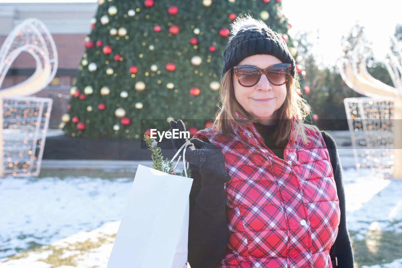 Portrait of woman standing against christmas tree during winter